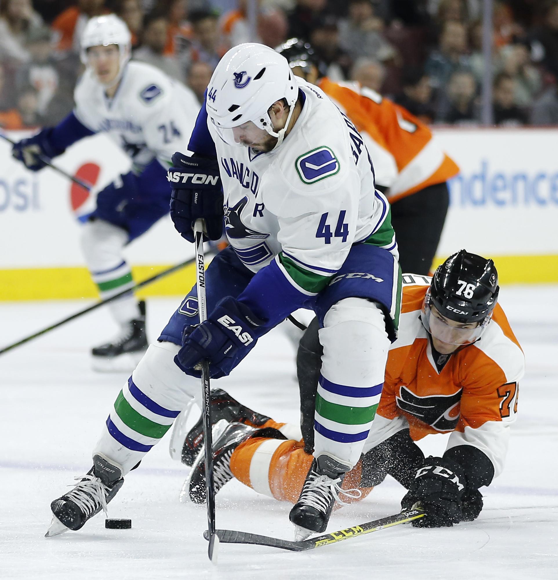 Philadelphia Flyers' Chris VandeVelde (76) knocks the pucks away from Vancouver Canucks' Matt Bartkowski (44) during the third period of an NHL hockey game, Thursday, Dec. 17, 2015, in Philadelphia. Philadelphia won 2-0. (AP Photo/Matt Slocum)