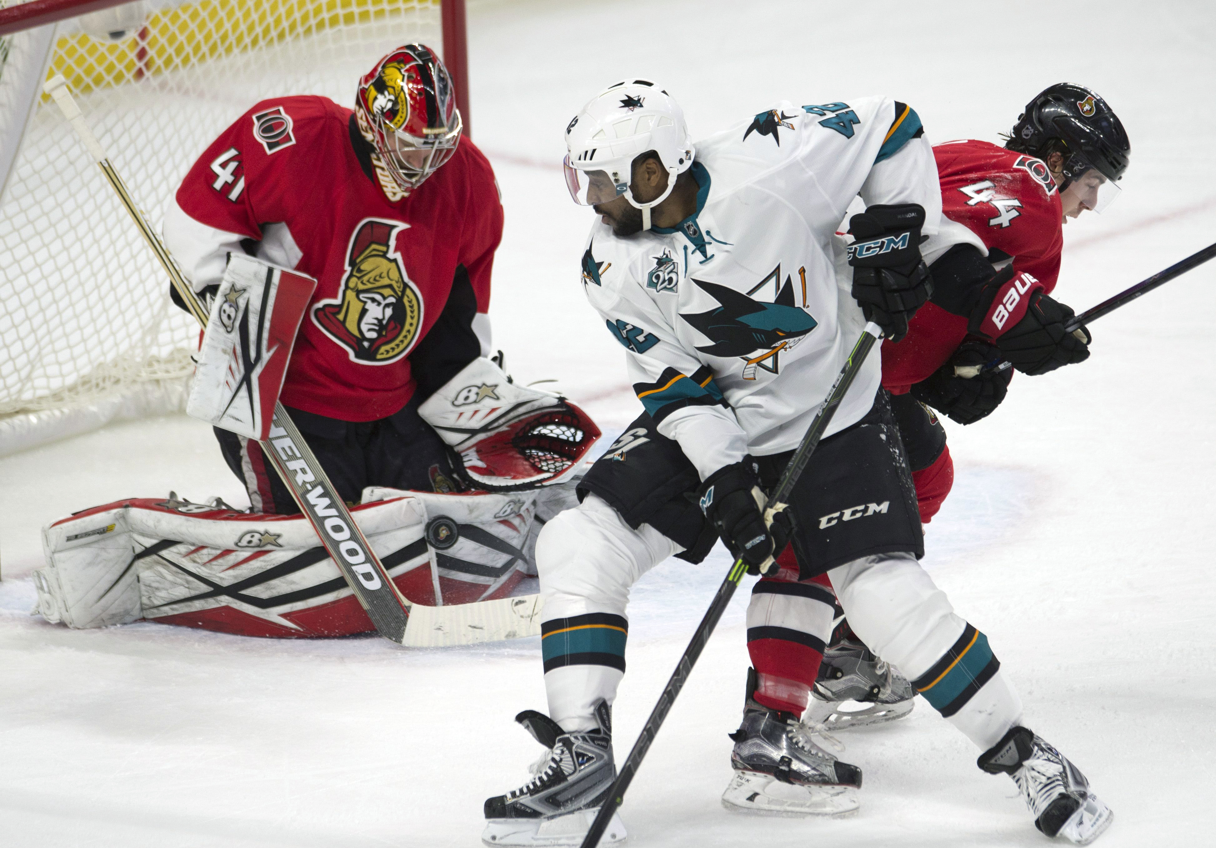 Ottawa Senators goalie Craig Anderson, left, makes a save as San Jose Sharks right wing Joel Ward, center, battles in front of the net with Senators center Jean-Gabriel Pageau during second-period NHL hockey game action Friday, Dec. 18, 2015, in Ottawa, O