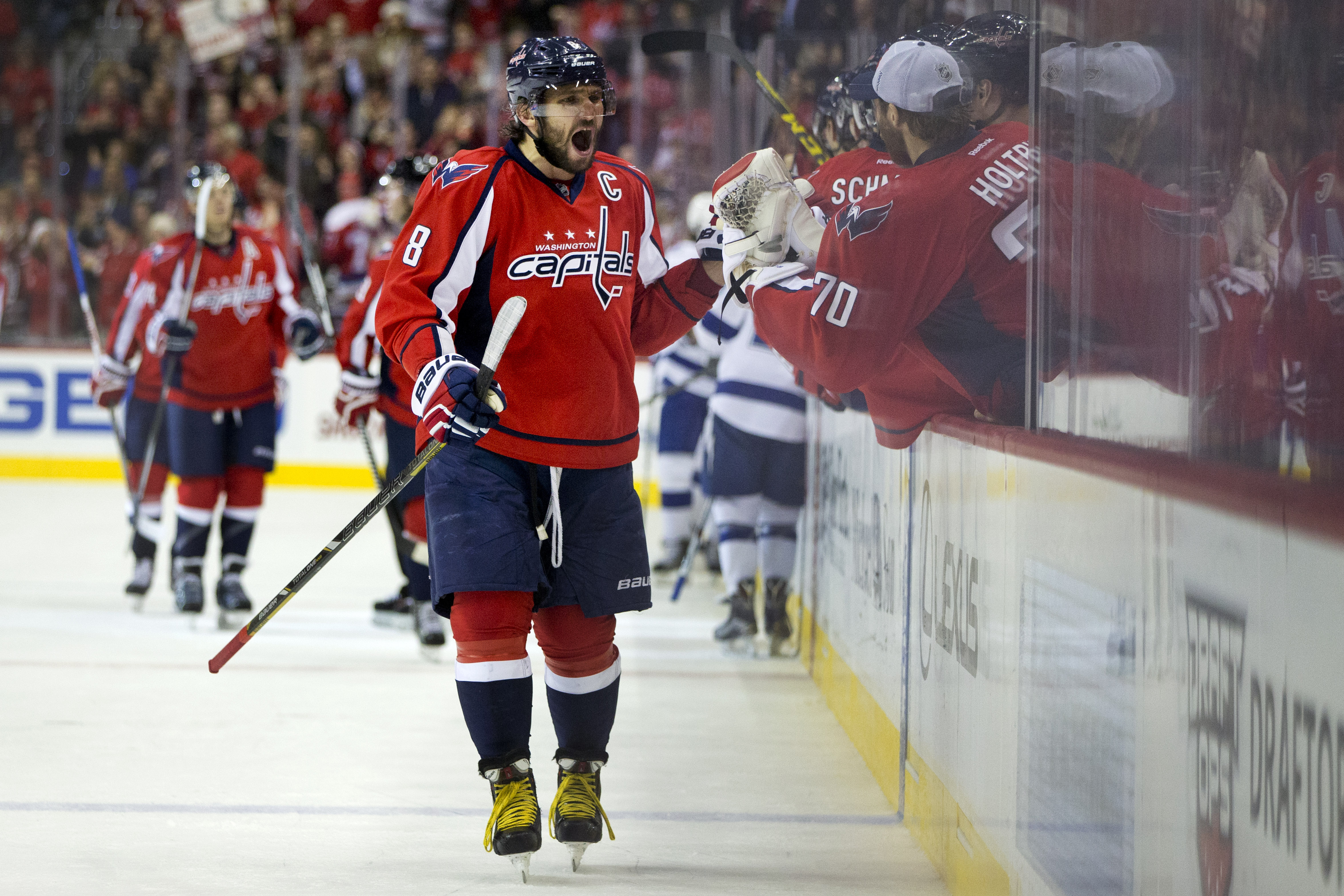 Washington Capitals left wing Alex Ovechkin (8), from Russia, high fives goalie Braden Holtby (70), as he reacts after the Capitals scored against the Tampa Bay Lightning during the third period of a hockey game at the Verizon Center in Washington on Frid