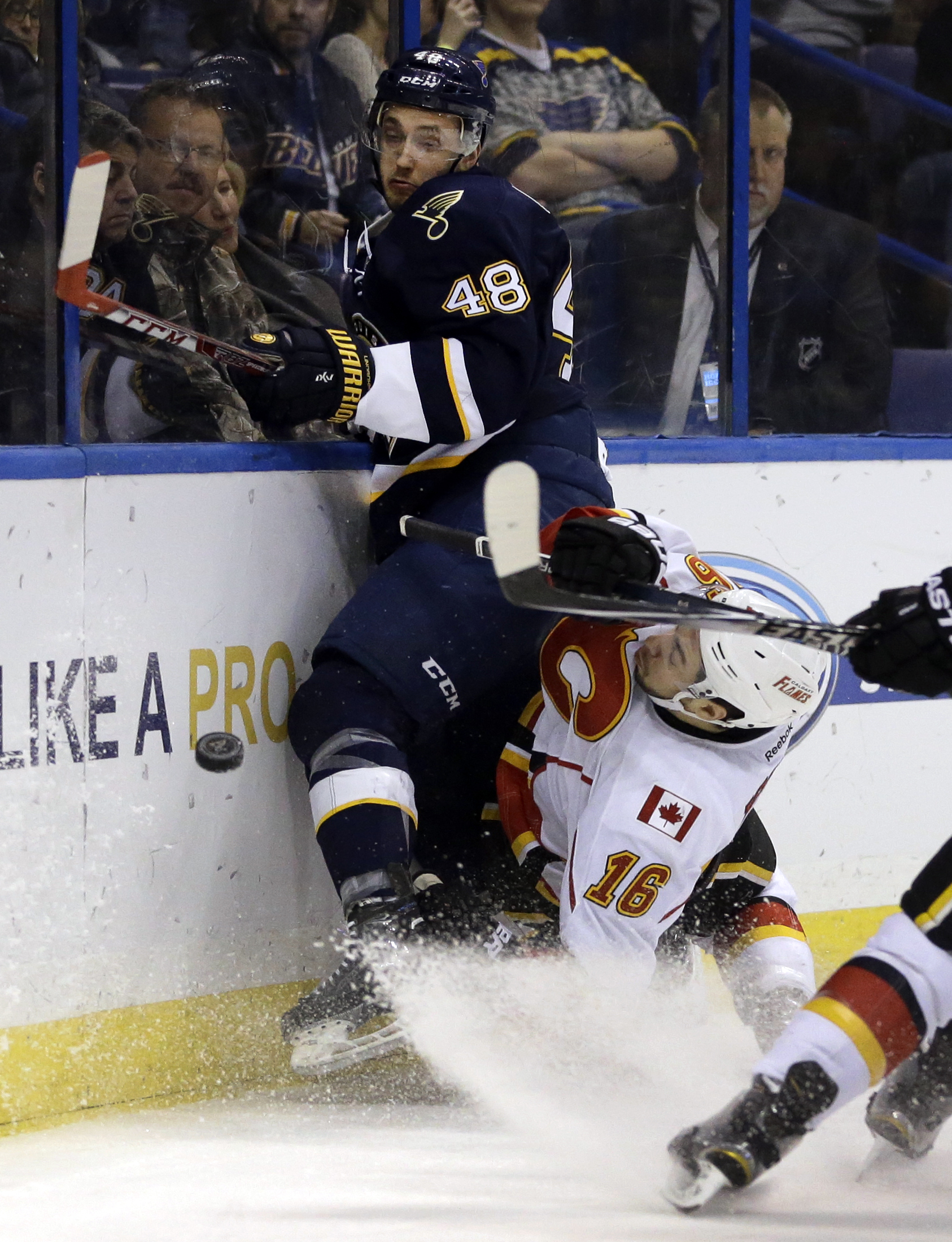 Calgary Flames' Josh Jooris, right, slams into the boards along with St. Louis Blues' Petteri Lindbohm, of Finland, during the first period of an NHL hockey game Saturday, Dec. 19, 2015, in St. Louis. (AP Photo/Jeff Roberson)