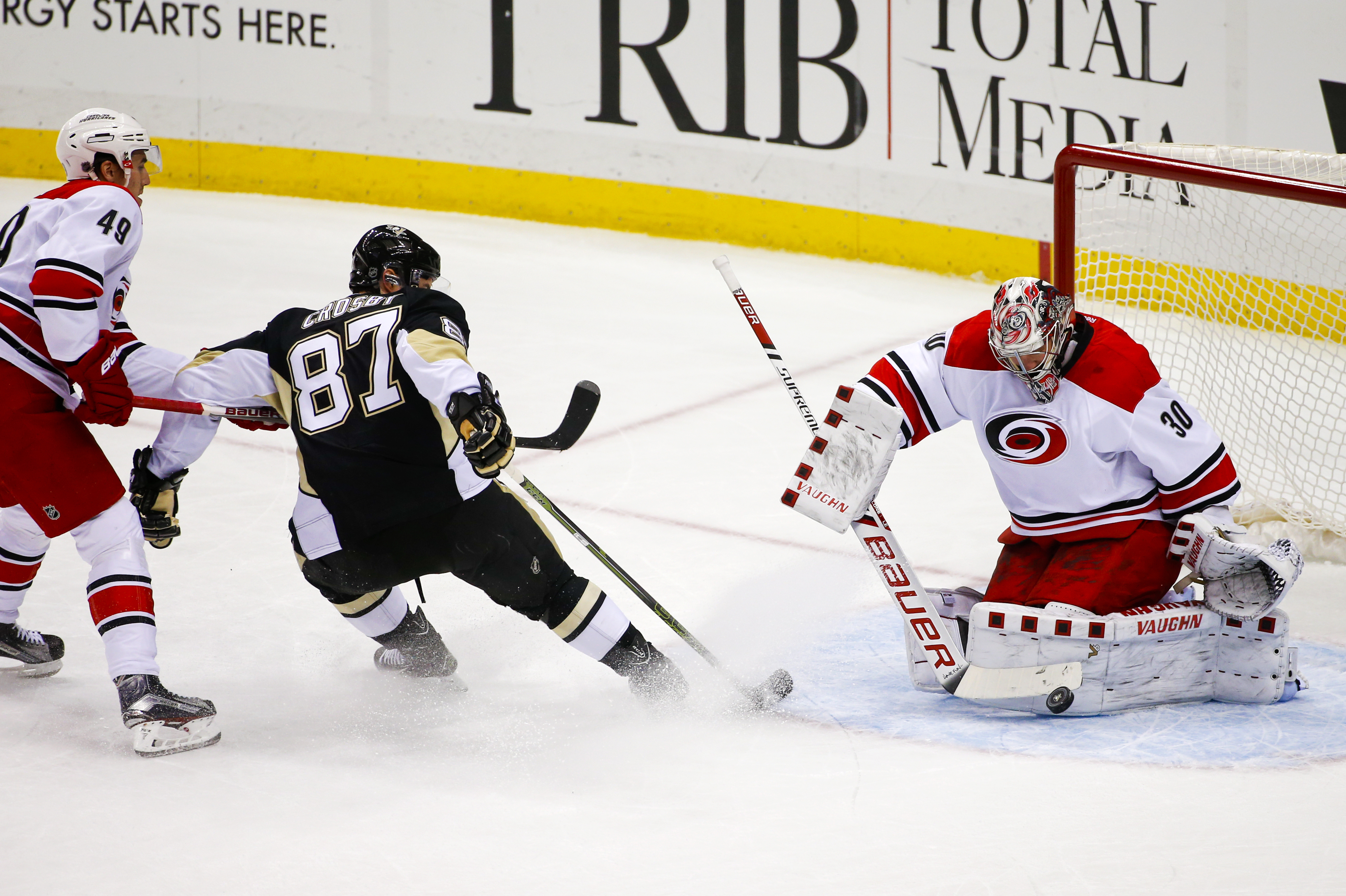 Carolina Hurricanes goalie Cam Ward (30) blocks a shot by Pittsburgh Penguins' Sidney Crosby (87) with Hurricanes' Victor Rask (49) also defending during the first period of an NHL hockey game in Pittsburgh, Saturday, Dec. 19, 2015. (AP Photo/Gene J. Pusk