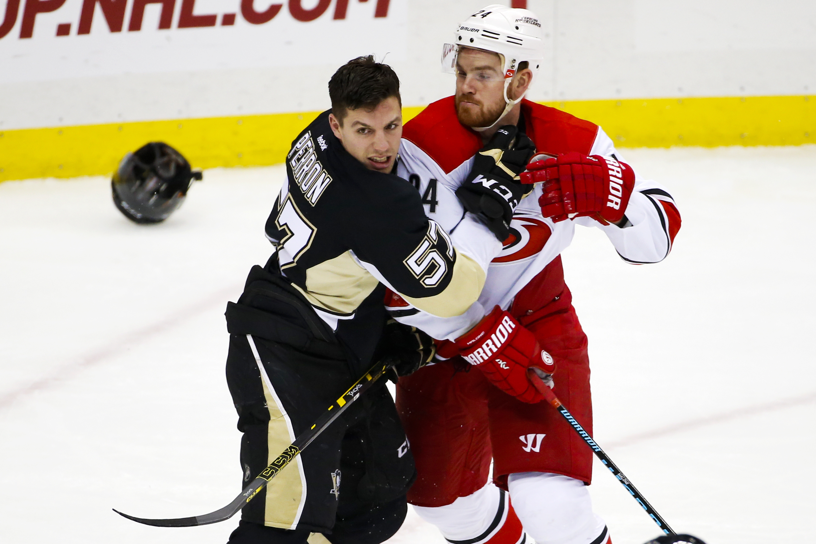 Pittsburgh Penguins' David Perron (57) and Carolina Hurricanes' Brad Malone (24) battle for position during the first period of an NHL hockey game in Pittsburgh, Saturday, Dec. 19, 2015. (AP Photo/Gene J. Puskar)