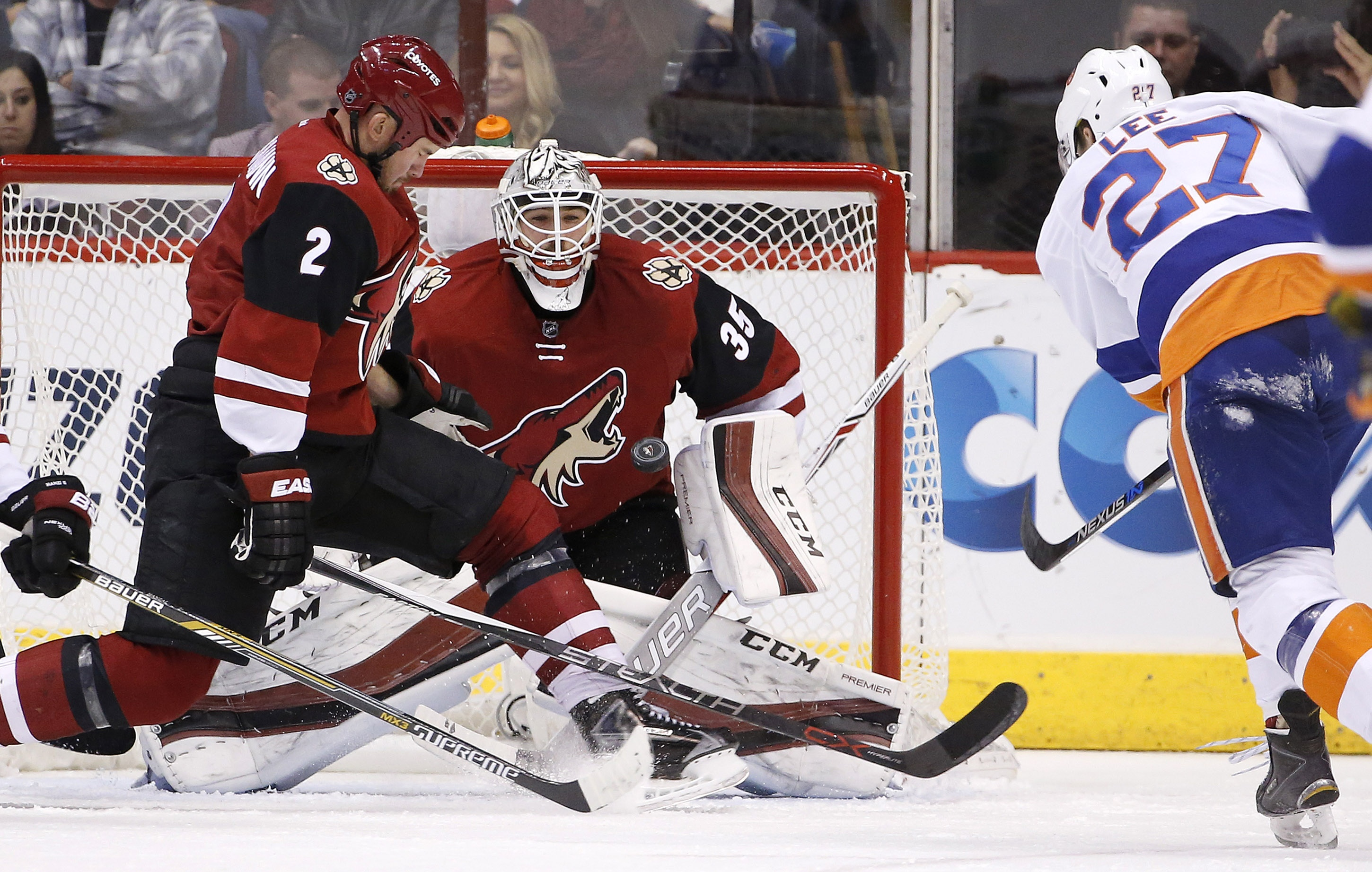 Arizona Coyotes' Louis Domingue (35) gets ready to make a save on a shot by New York Islanders' Anders Lee (27) as Coyotes' Nicklas Grossmann (2), of Sweden, slides over in an attempt to deflect the puck during the second period of an NHL hockey game Satu