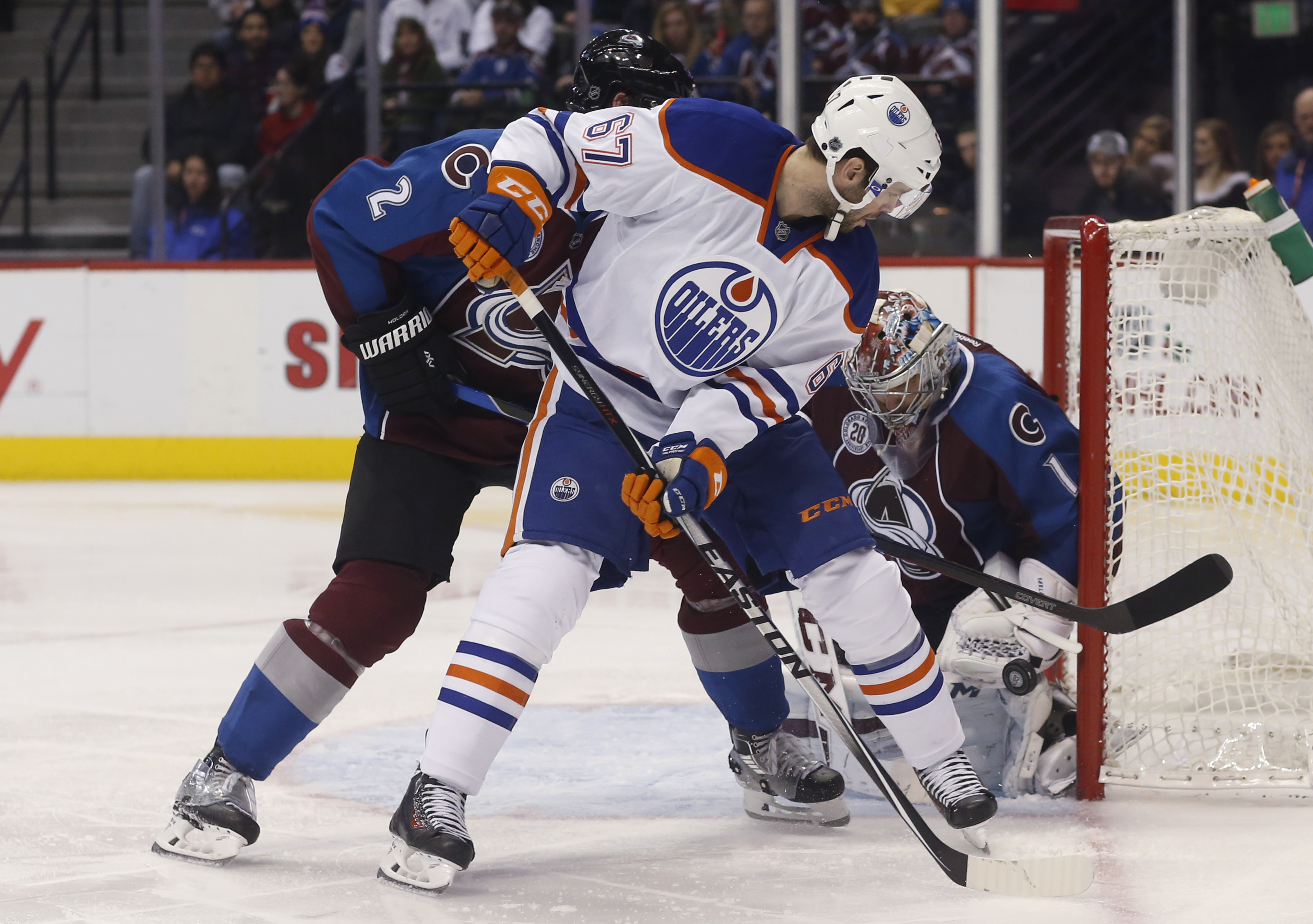 Edmonton Oilers left wing Benoit Pouliot, front, redirects a shot past Colorado Avalanche defenseman Nick Holden, left, toward goalie Semyon Varlamov, of Russia, during the third period of an NHL hockey game Saturday, Dec. 19, 2015, in Denver. Colorado wo
