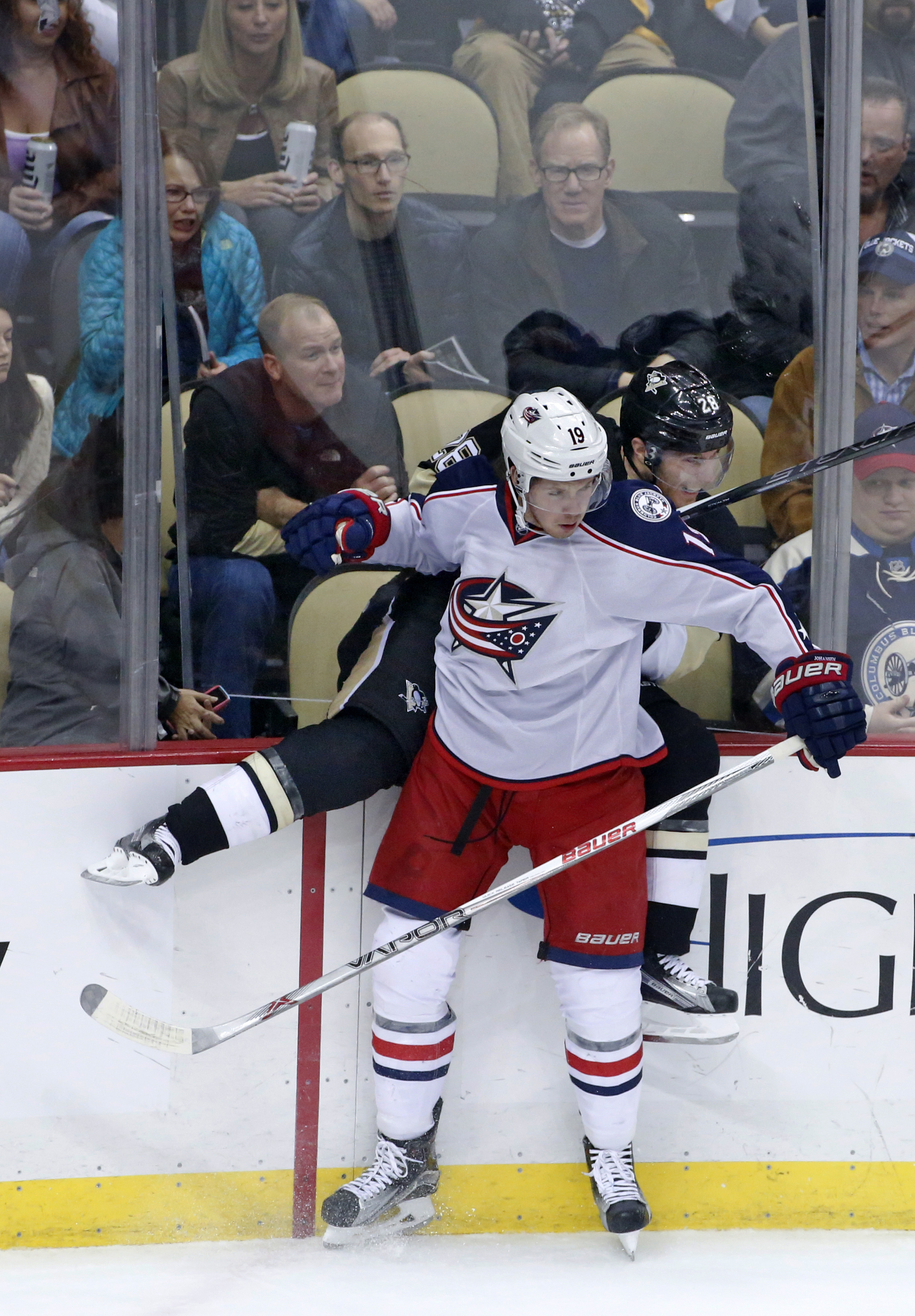 Columbus Blue Jackets' Ryan Johansen (19) checks Pittsburgh Penguins' Ian Cole (28), dislodging the glass into the seats during the first period of an NHL hockey game in Pittsburgh, Monday, Dec. 21, 2015. There were no apparent injuries. (AP Photo/Gene J.