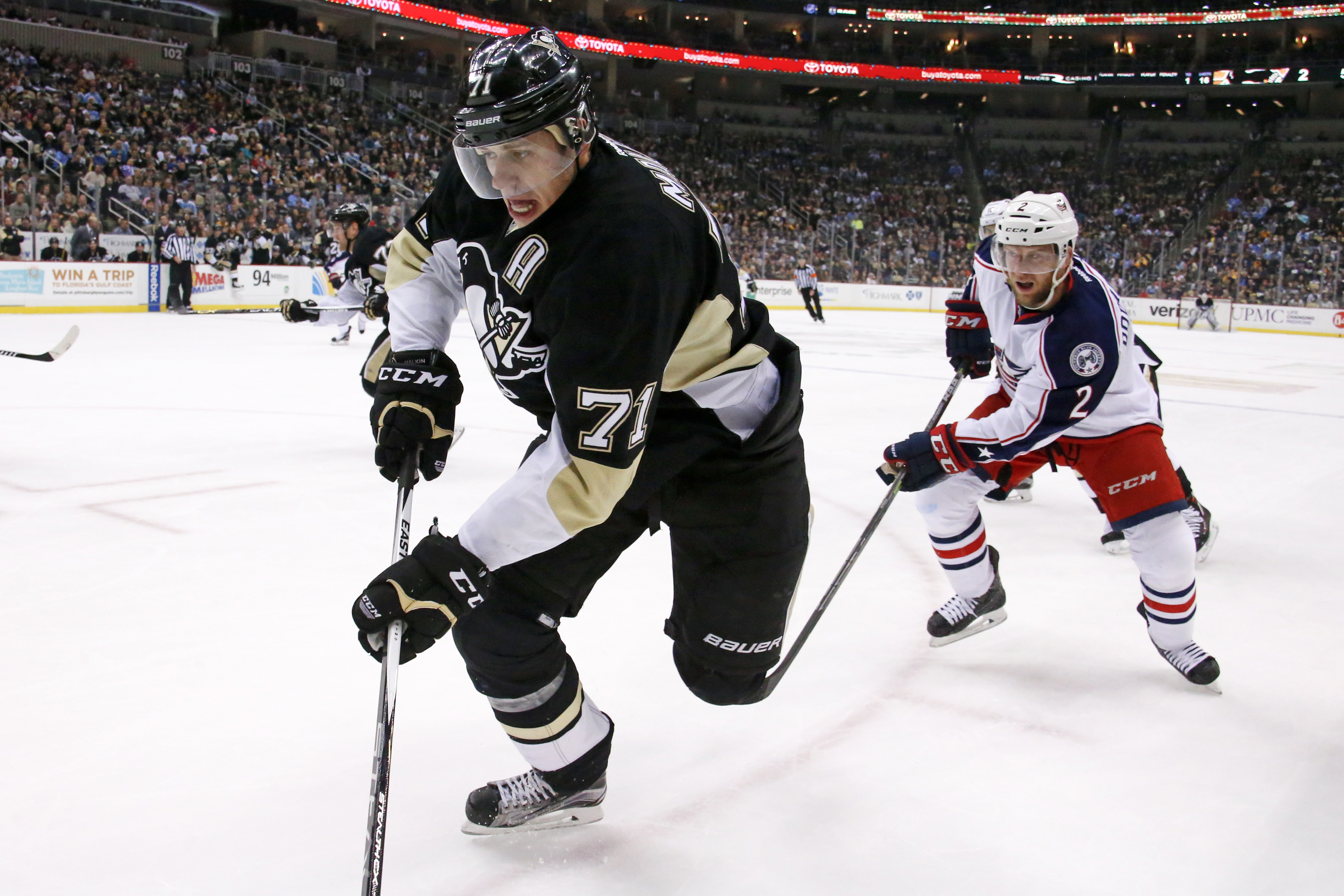 Pittsburgh Penguins' Evgeni Malkin (71) works the puck in the corner against Columbus Blue Jackets' Andrew Bodnarchuk (2) during the second period of an NHL hockey game in Pittsburgh, Monday, Dec. 21, 2015. (AP Photo/Gene J. Puskar)