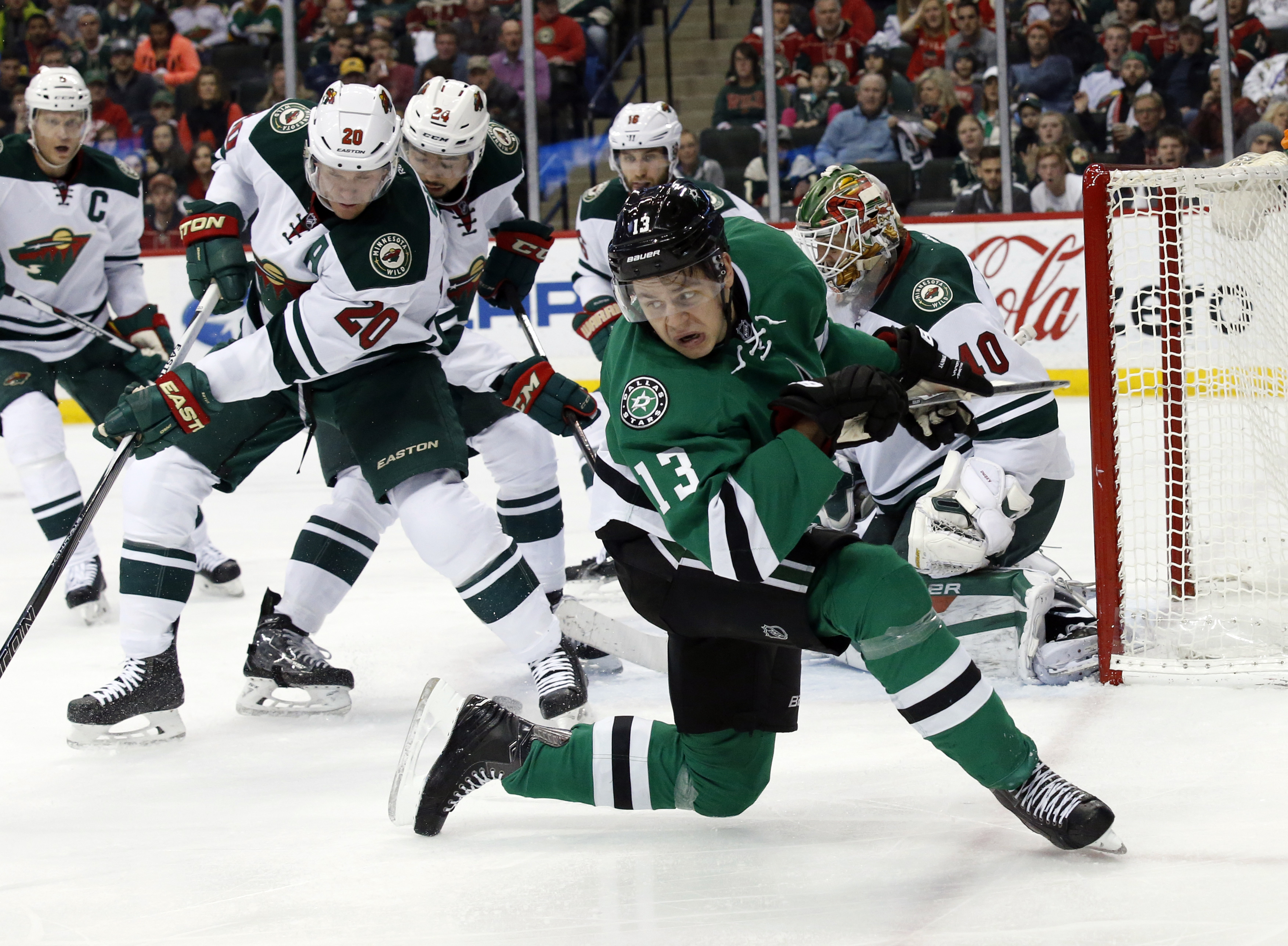 Dallas Stars center Mattias Janmark (13), from Sweden, spins around to look for the rebounding puck with Minnesota Wild defenseman Ryan Suter (20), Wild goalie Devan Dubnyk (40), and others behind, in the second period of an NHL hockey game, Monday, Dec.