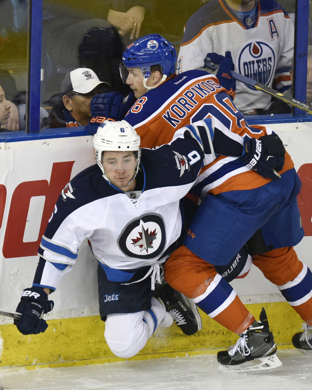 Edmonton Oilers' Lauri Korpikoski (28) checks Winnipeg Jets' Alexander Burmistrov (6) during the third period of an NHL hockey game Monday, Dec. 21, 2015, in Edmonton, Alberta. The Oilers won 3-1. (John Ulan/The Canadian Press via AP)
