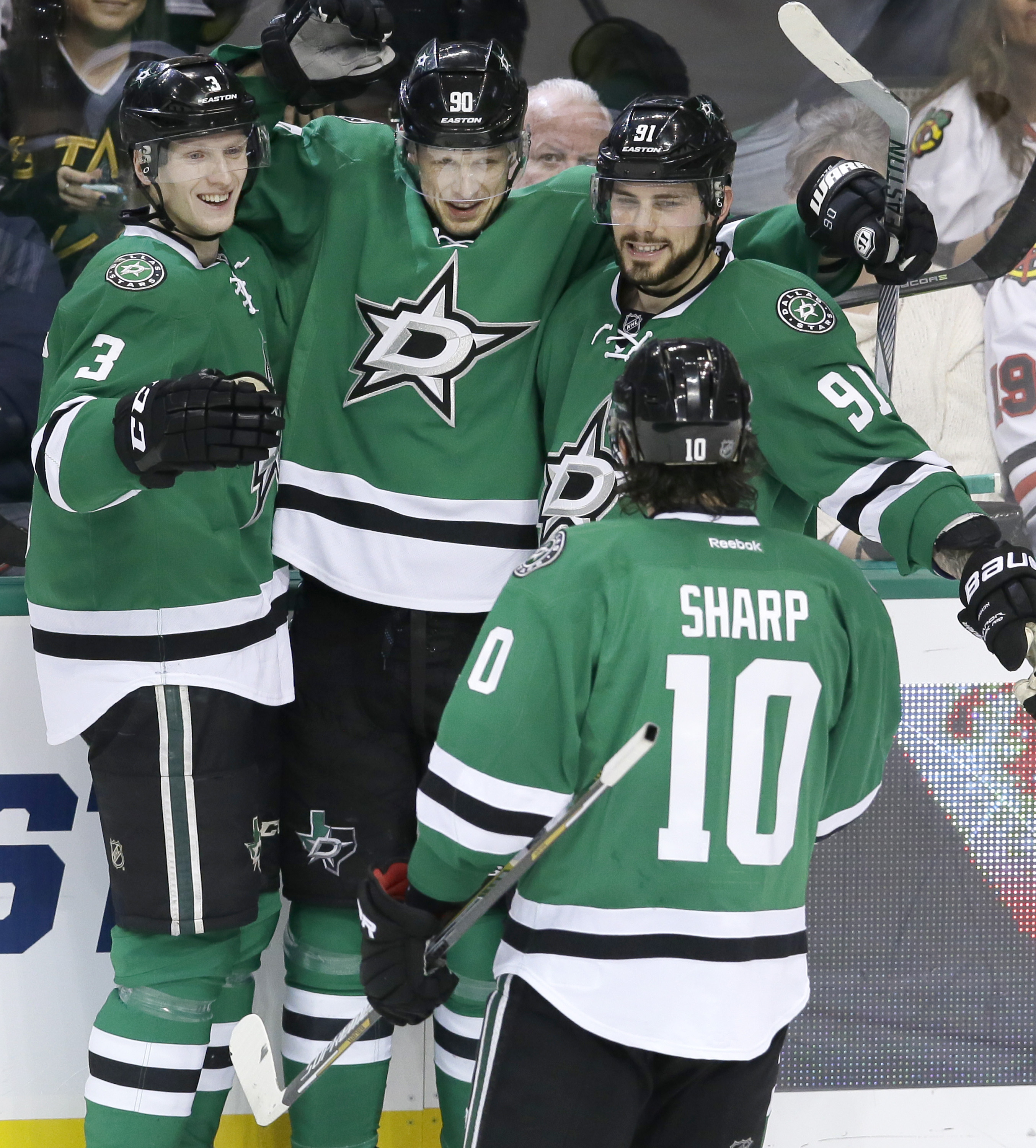 Dallas Stars center Jason Spezza (90) celebrates scoring a goal with teammates John Klingberg (3), Tyler Seguin (91) and Patrick Sharp (10) during the second period of an NHL hockey game against the Chicago Blackhawks on Tuesday, Dec. 22, 2015, in Dallas.