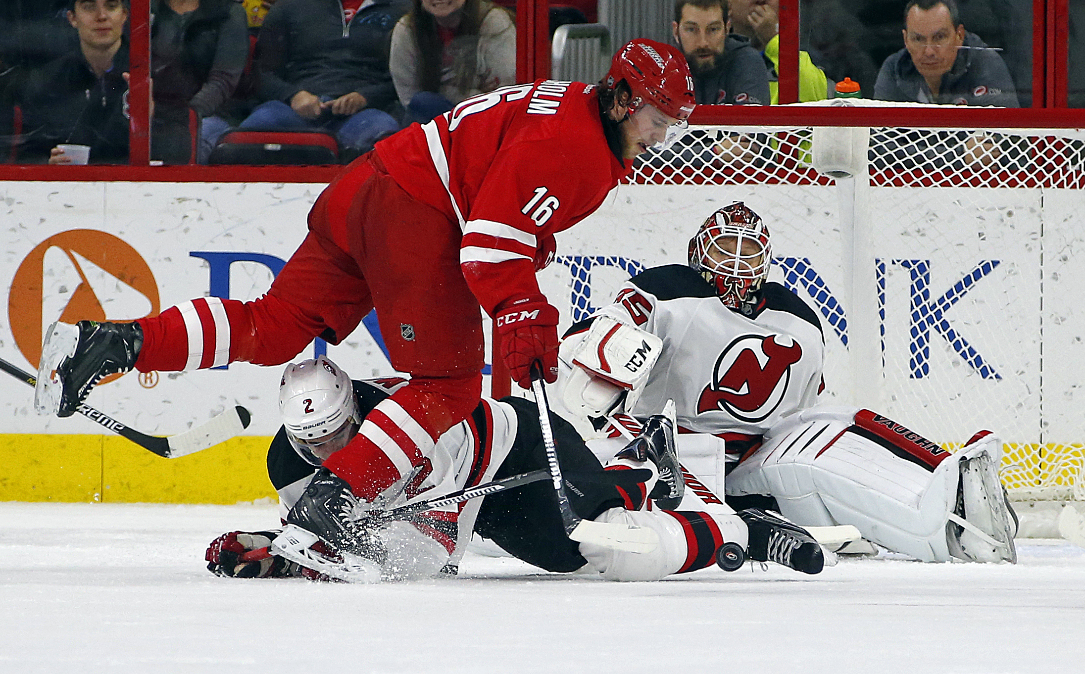 Carolina Hurricanes' Elias Lindholm (16) of Sweden, collides with New Jersey Devils' Adam Larsson (5) in front of goalie Cory Schneider (35) during the second period of an NHL hockey game, Saturday, Dec. 26, 2015, in Raleigh, N.C. (AP Photo/Karl B DeBlake