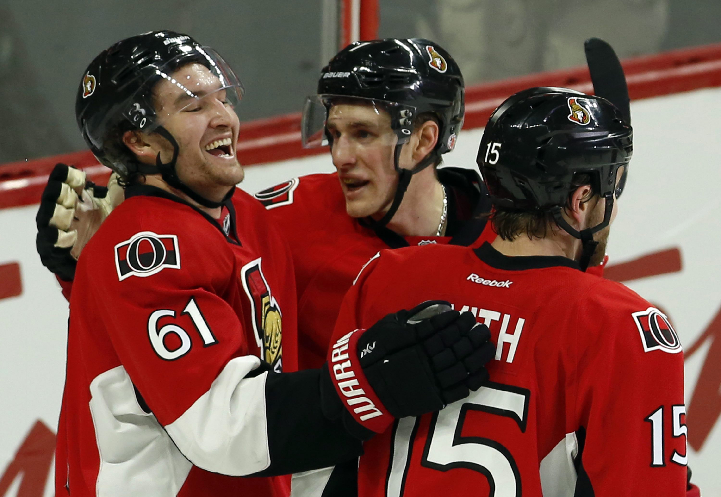 Ottawa Senators' Mark Stone (61) celebrates his goal with teammates Kyle Turris (7) and Zack Smith (15) during first period NHL hockey action against the Boston Bruins in Ottawa on Sunday, Dec. 27, 2015. (Fred Chartrand/The Canadian Press via AP)