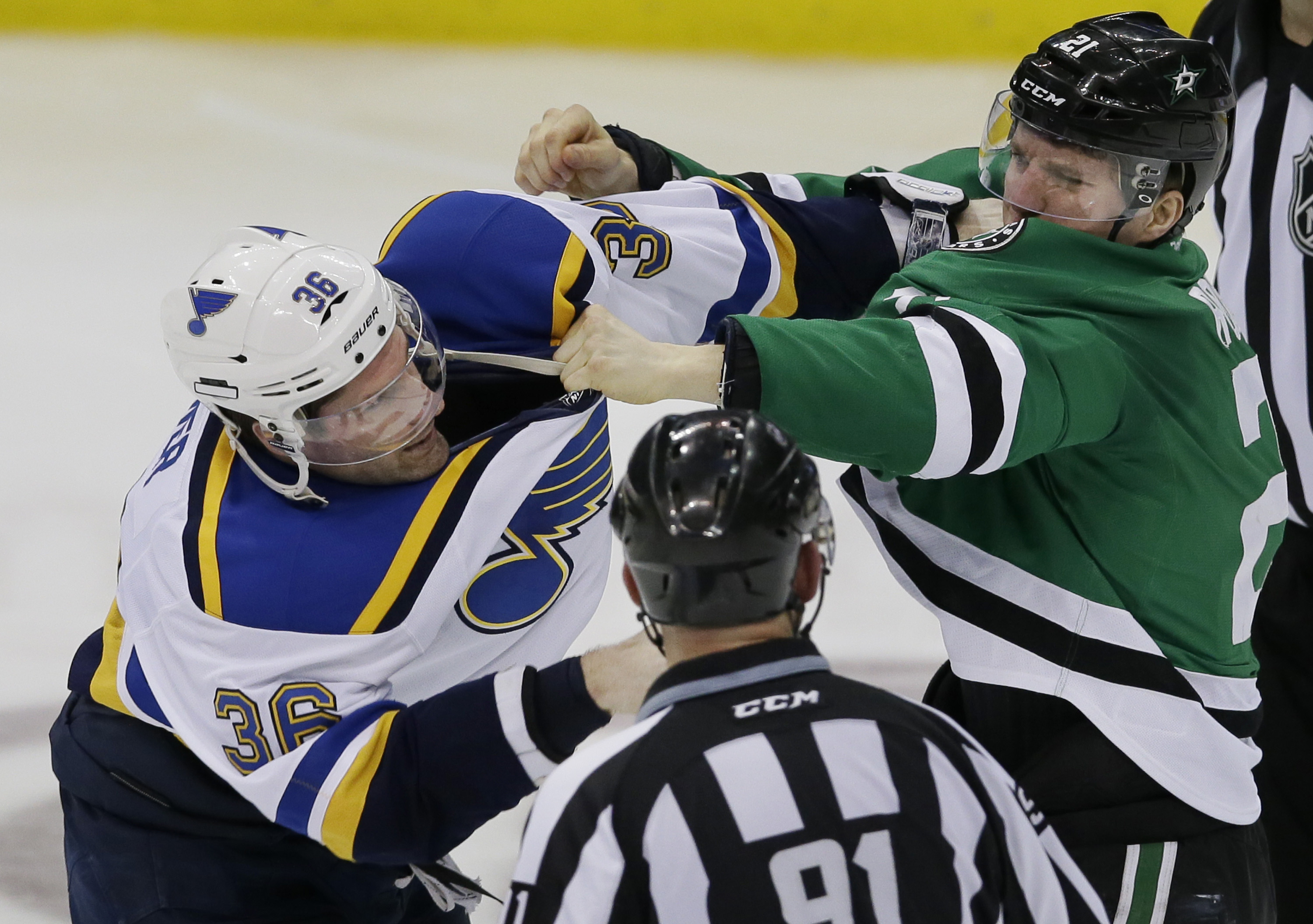 St. Louis Blues right wing Troy Brouwer (36) and Dallas Stars left wing Antoine Roussel (21) fight during the second period of an NHL hockey game Sunday, Dec. 27, 2015, in Dallas. (AP Photo/LM Otero)