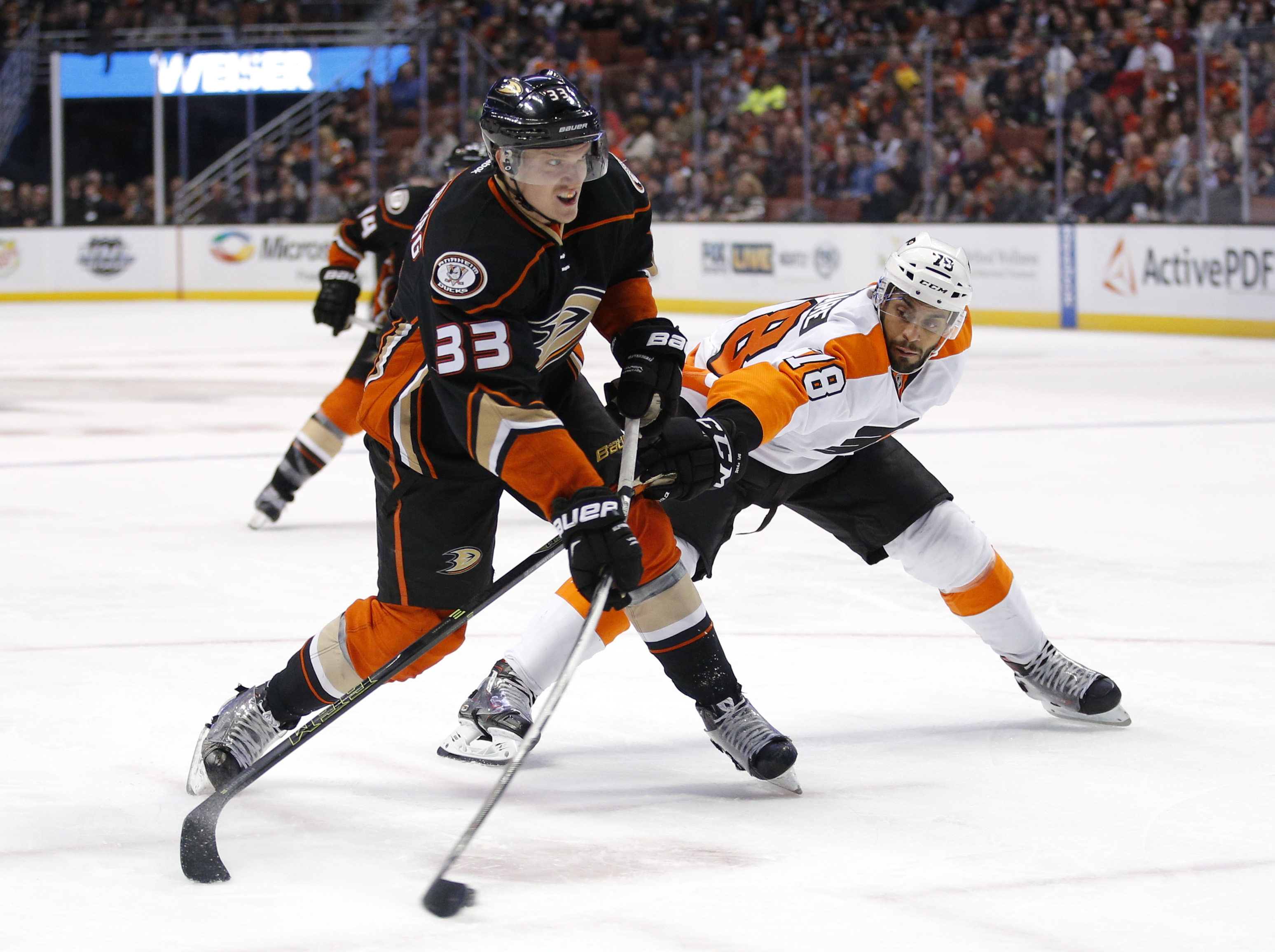 Anaheim Ducks' Jakob Silfverberg, left, of Sweden, shoots as he is defended by Philadelphia Flyers' Pierre-Edouard Bellemare, of France, during the second period of an NHL hockey game, Sunday, Dec. 27, 2015, in Anaheim, Calif. (AP Photo/Jae C. Hong)