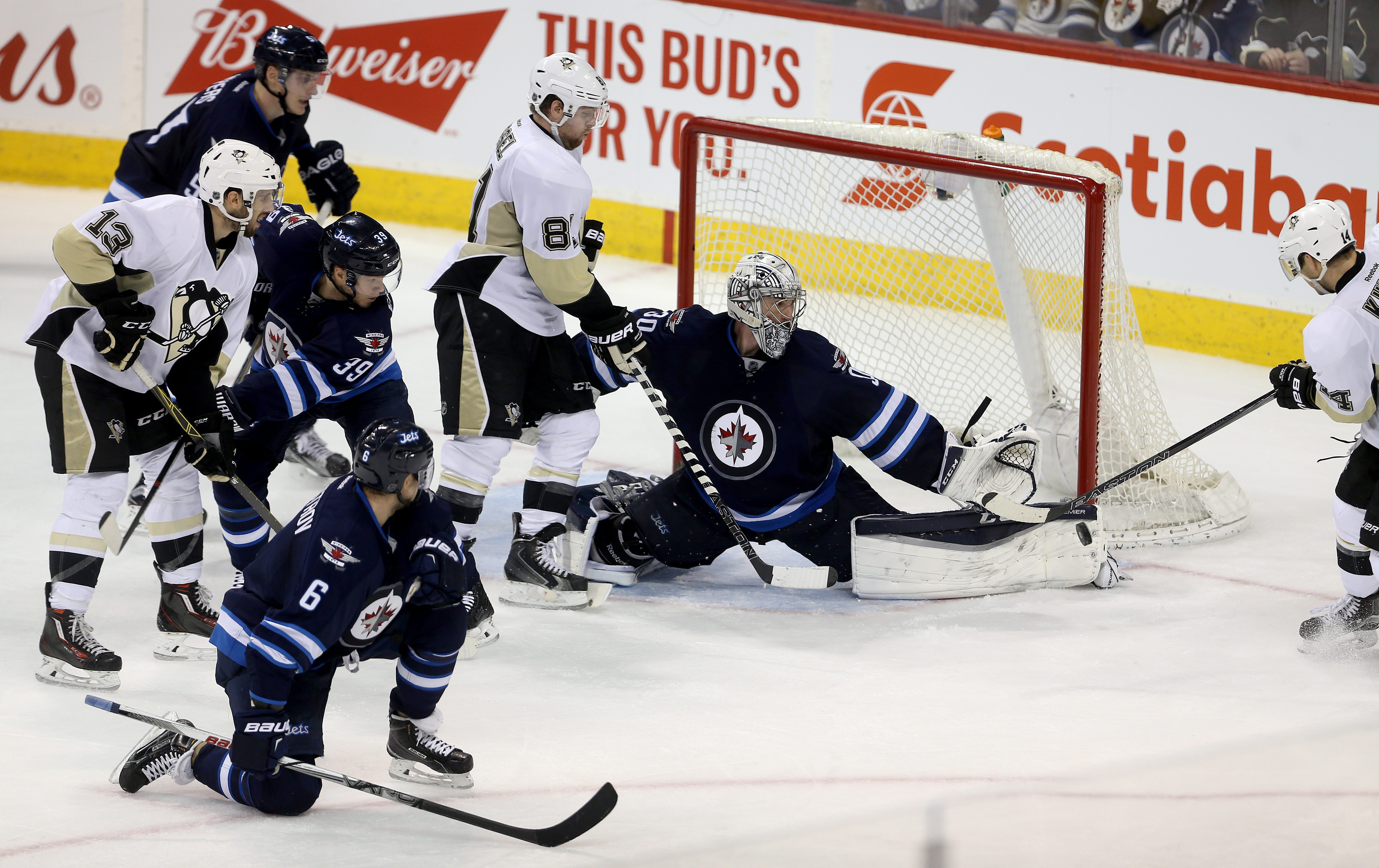Winnipeg Jets' goaltender Connor Hellebuyck (30) stops the puck during the third period of an NHL hockey game against the Pittsburgh Penguins in Winnipeg, Manitoba, Sunday, Dec. 27, 2015. The Jets won 1-0. (Trevor Hagan/The Canadian Press via AP) MANDATOR