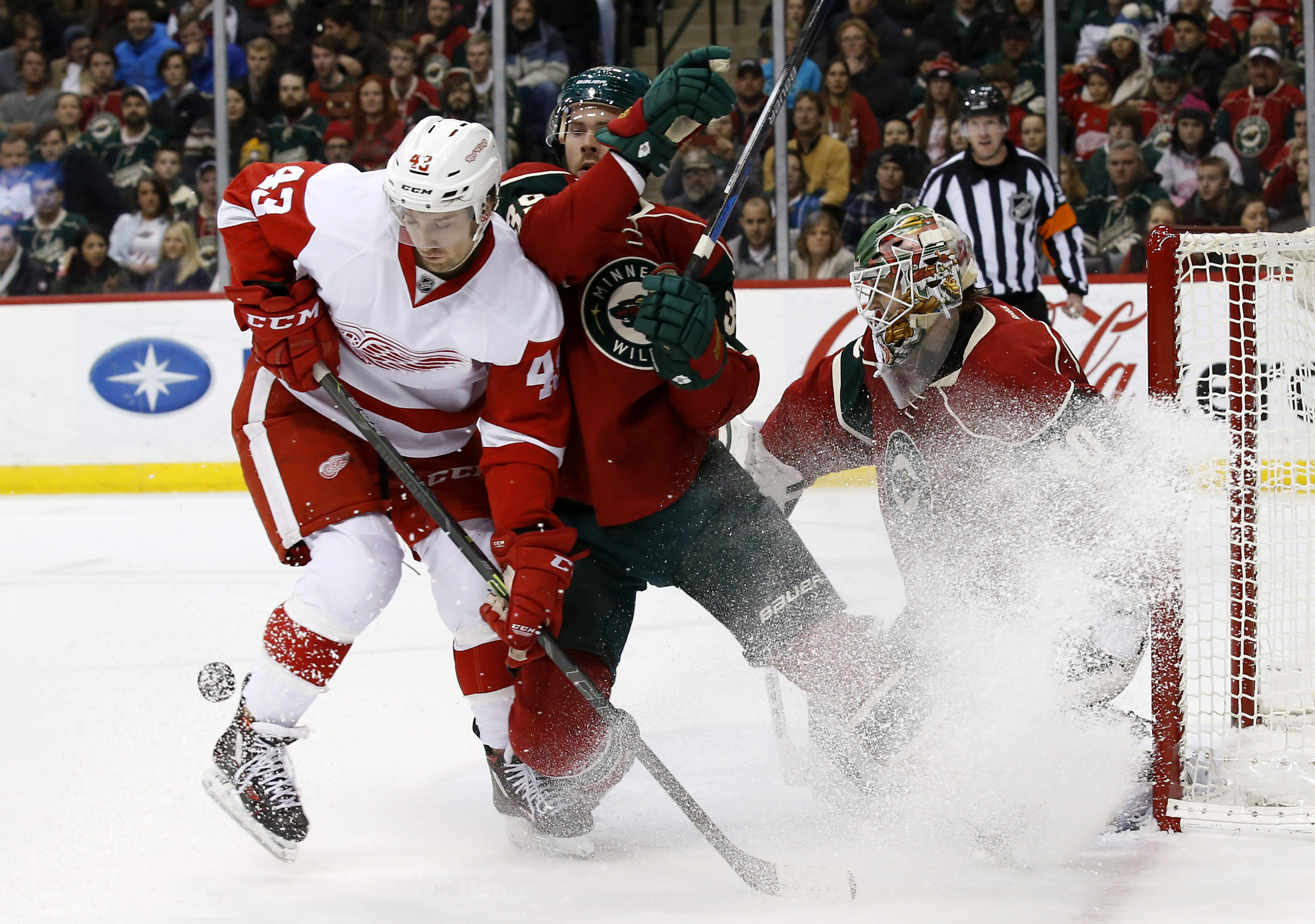 Detroit Red Wings center Darren Helm (43) and Minnesota Wild defenseman Nate Prosser compete for the puck in front of Wild goalie Devan Dubnyk during the second period of an NHL hockey game in St. Paul, Minn., Monday, Dec. 28, 2015. (AP Photo/Ann Heisenfe