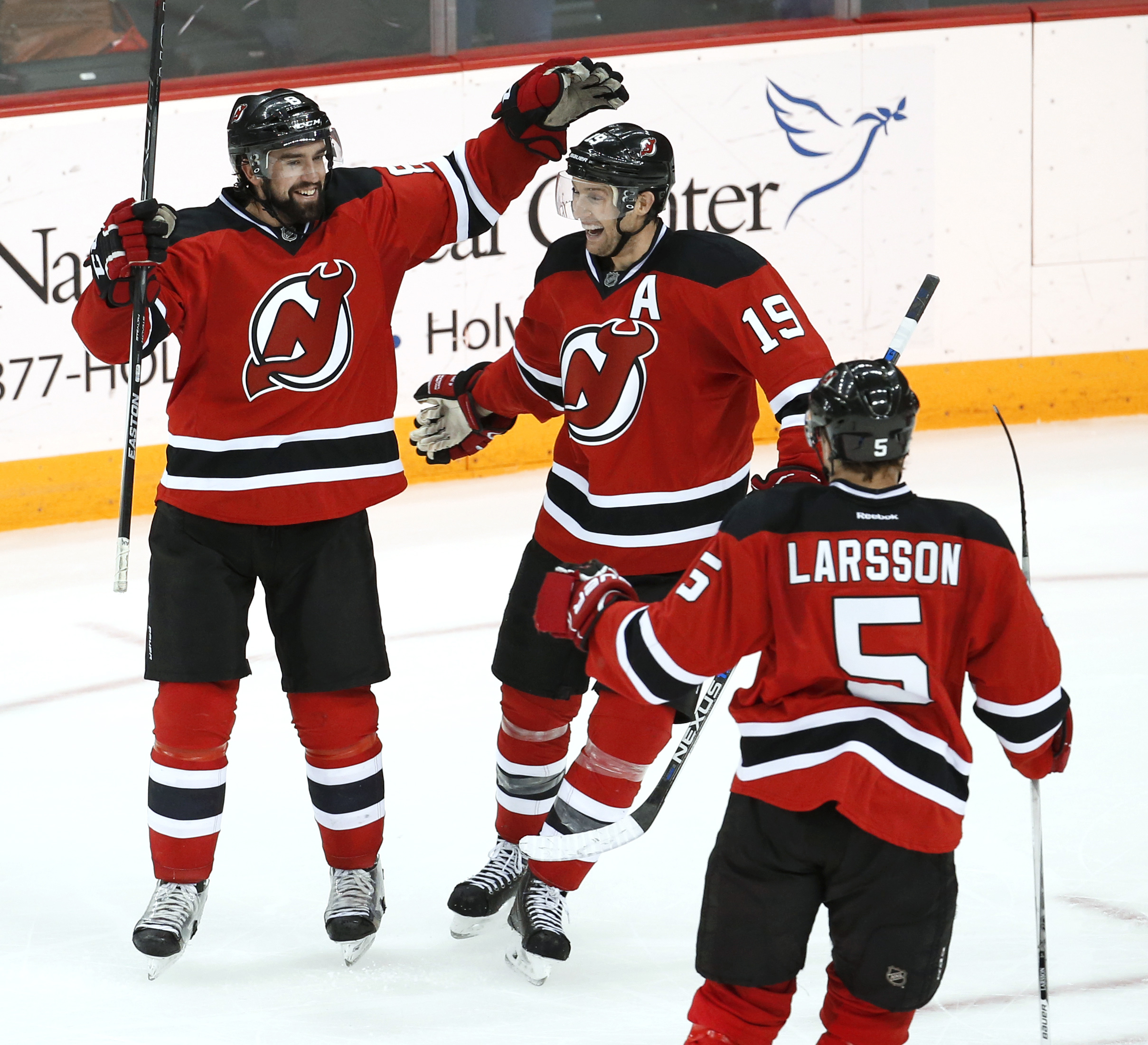 New Jersey Devils' David Schlemko, left, Travis Zajac, center, and Adam Larsson, of Sweden, celebrate Schlemko's goal against the Carolina Hurricanes during the third period of an NHL hockey game, Tuesday, Dec. 29, 2015, in Newark, N.J. The Devils won 3-2