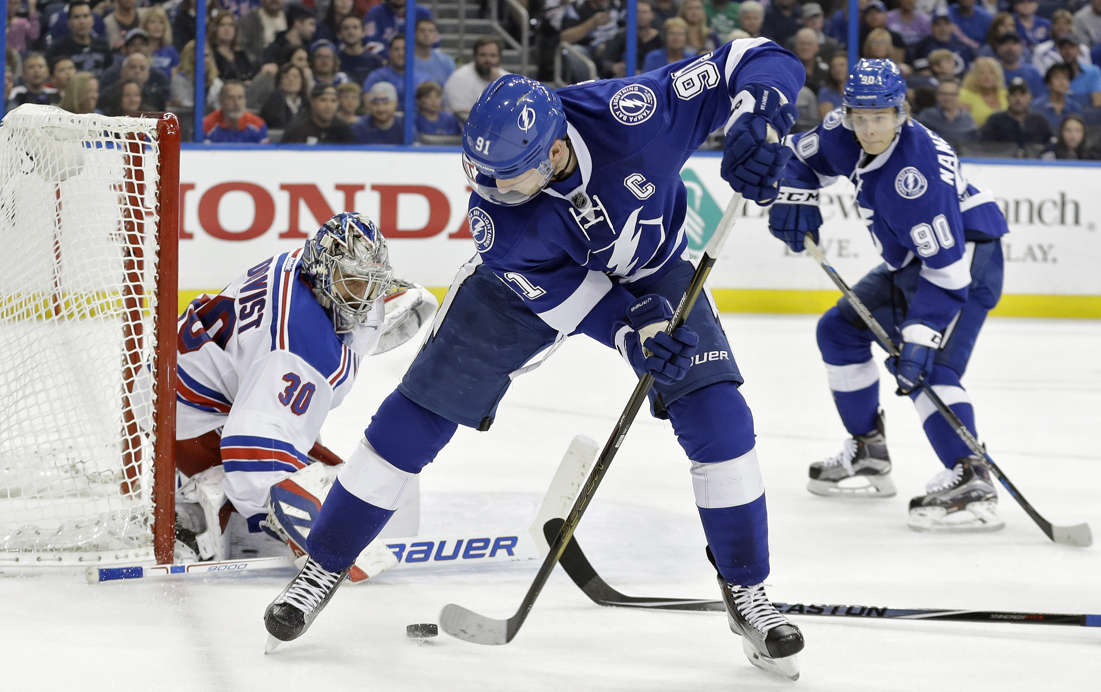 Tampa Bay Lightning center Steven Stamkos (91) shoots the puck against New York Rangers goalie Henrik Lundqvist, of Sweden, during the second period of an NHL hockey game Wednesday, Dec. 30, 2015, in Tampa, Fla. Looking for a rebound is Lightning's center