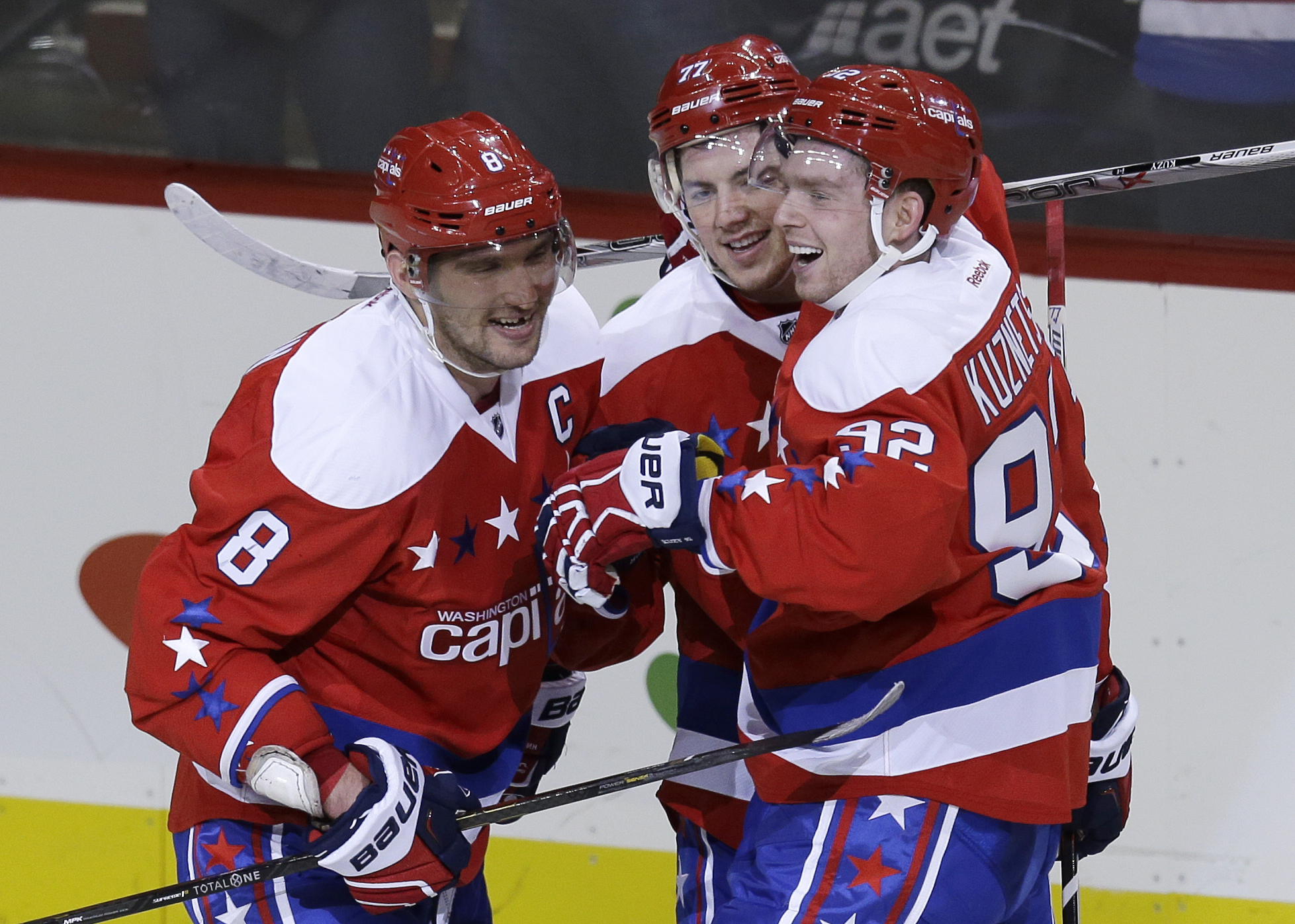 Washington Capitals left wing Alex Ovechkin (8) celebrates scoring an empty net goal with teammates T.J. Oshie (77), and Evgeny Kuznetsov (92) during the third period of an NHL hockey game against Buffalo Sabres, Wednesday, Dec. 30, 2015, in Washington. O