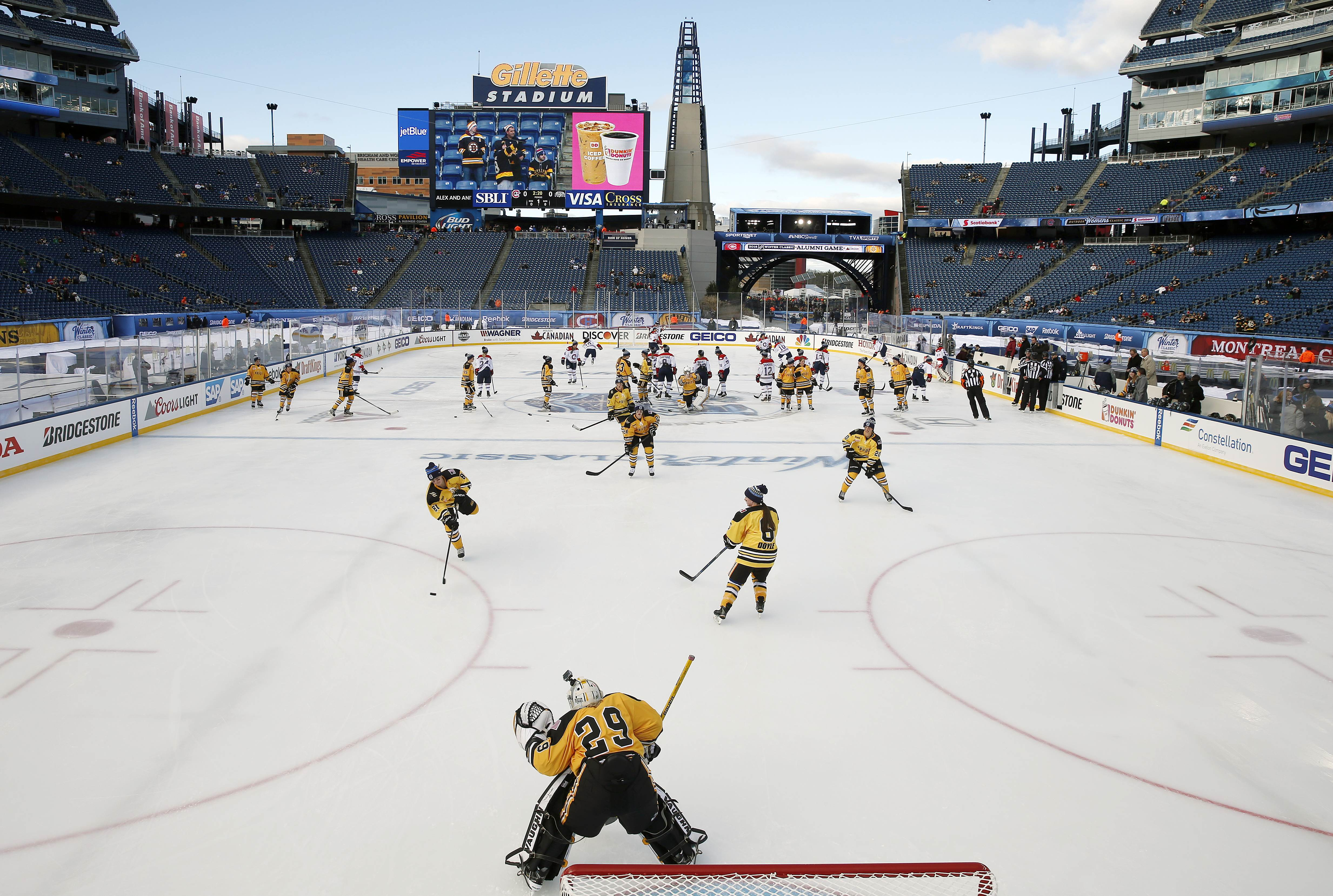 The Boston Pride, foreground, warm up before a women's outdoor hockey game against the Montreal Les Canadiennes at Gillette Stadium in Foxborough, Mass., Thursday, Dec. 31, 2015, where the Boston Bruins will play the Montreal Canadiens in the NHL Winter C
