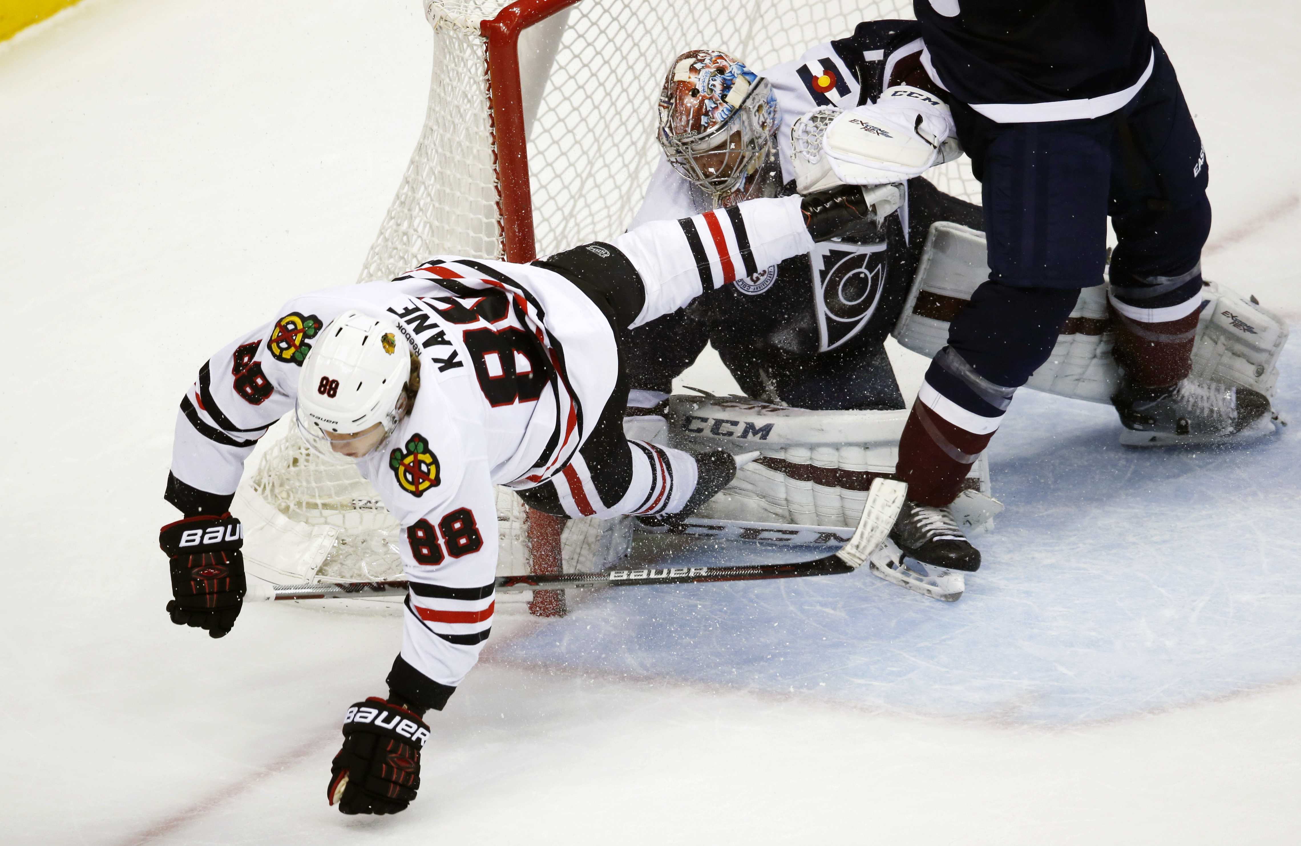 Chicago Blackhawks right wing Patrick Kane, left, careens off Colorado Avalanche goalie Semyon Varlamov, of Russia, after Varlamov stopped his shot in overtime of an NHL hockey game Thursday, Dec. 31, 2015, in Denver. Chicago won 4-3. (AP Photo/David Zalu
