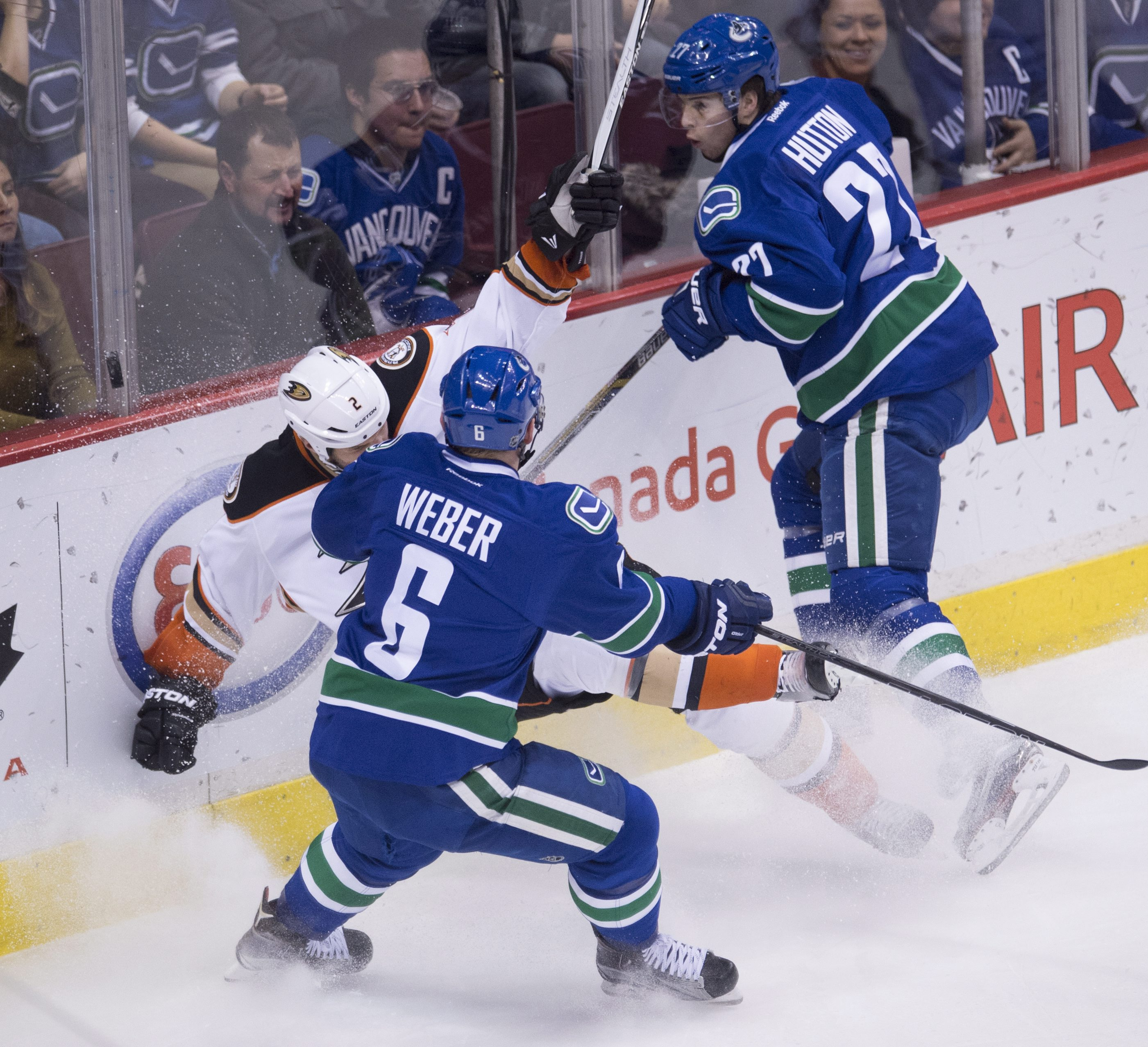 Vancouver Canucks defenseman Yannick Weber (6) and defenseman Ben Hutton (27) go into the boards with Anaheim Ducks defenseman Kevin Bieksa (2) during the second period of an NHL hockey game in Vancouver, British Columbia, Friday, Jan. 1, 2016.  (Jonathan