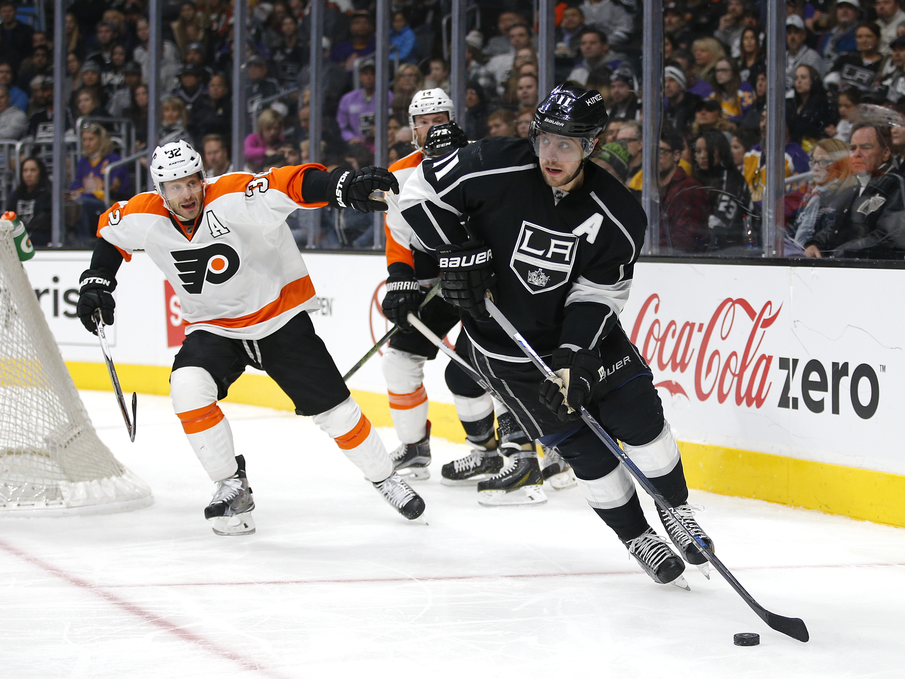 Los Angeles Kings' Anze Kopitar, right, of Slovenia, moves the puck past Philadelphia Flyers' Mark Streit, of Switzerland, during the second period of an NHL hockey game, Saturday, Jan. 2, 2016, in Los Angeles. (AP Photo/Jae C. Hong)