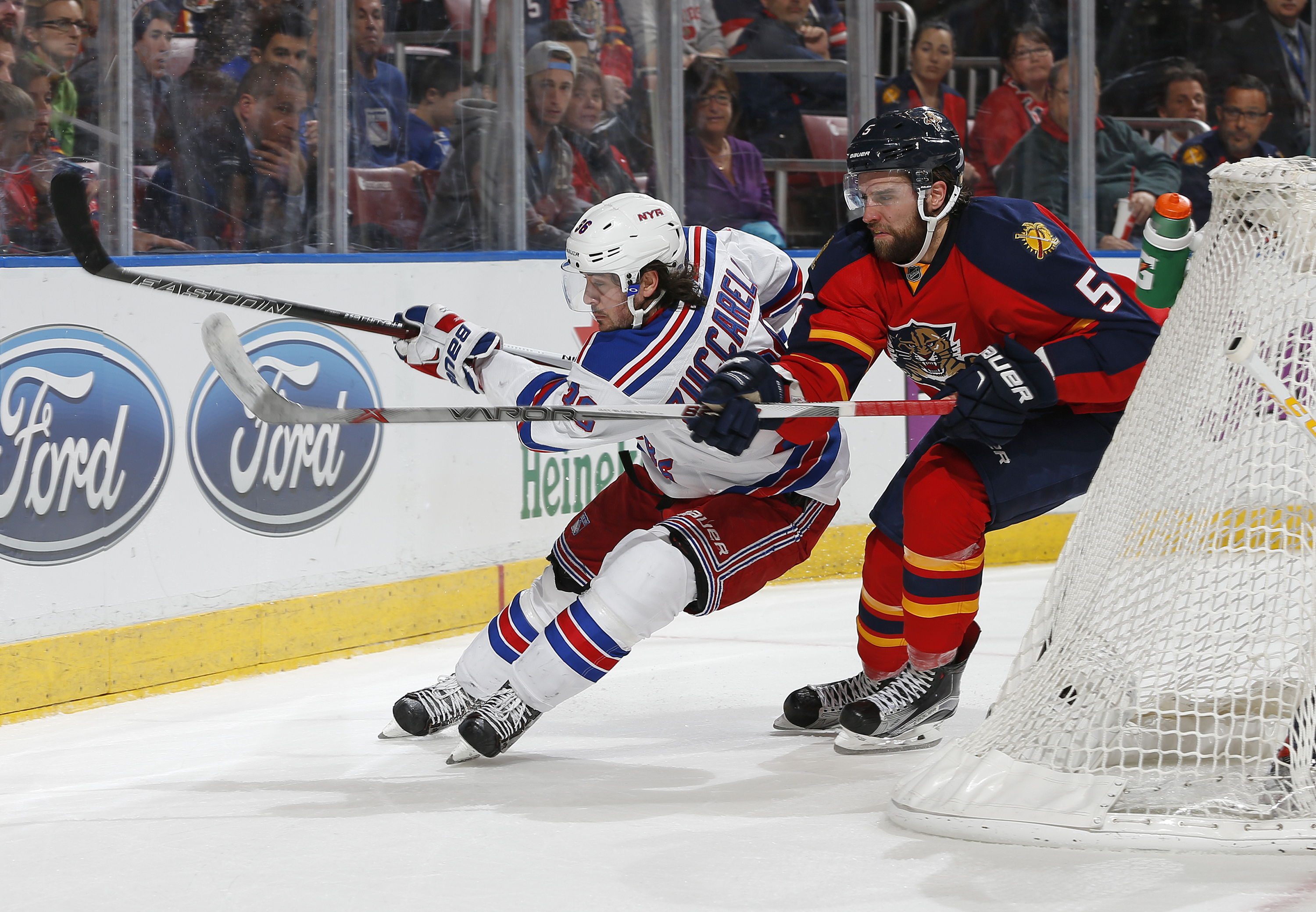 New York Rangers forward Mats Zuccarello (36) and Florida Panthers defenseman Aaron Ekblad (5) chase a loose puck as they skate behind the net during the second period of an NHL hockey game, Saturday, Jan. 2, 2016, in Sunrise, Fla. (AP Photo/Joel Auerbach