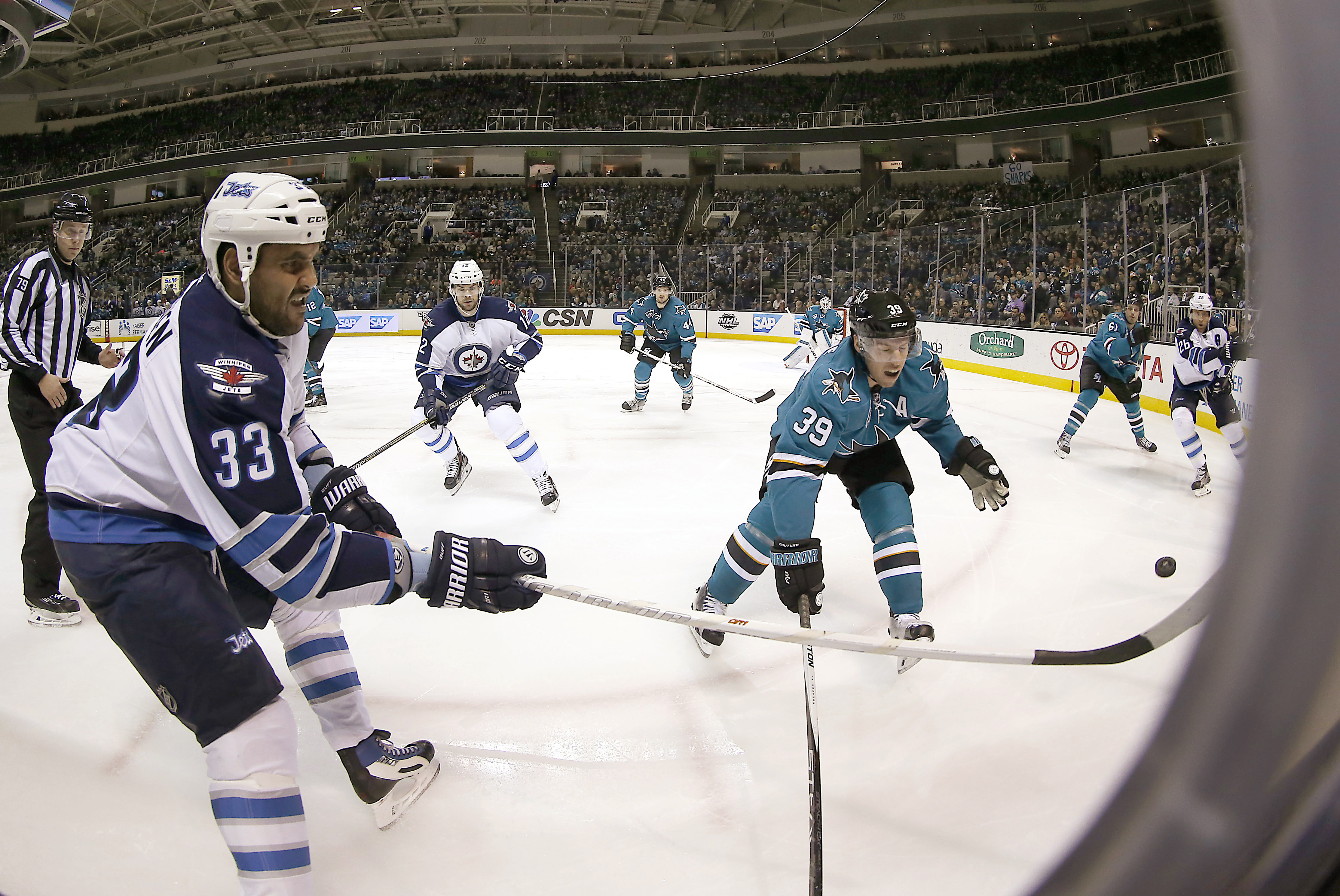 Winnipeg Jets' Dustin Byfuglien (33) passes the puck past San Jose Sharks' Logan Couture (39) during the second period of an NHL hockey game Saturday, Jan. 2, 2016, in San Jose, Calif. (AP Photo/Tony Avelar)