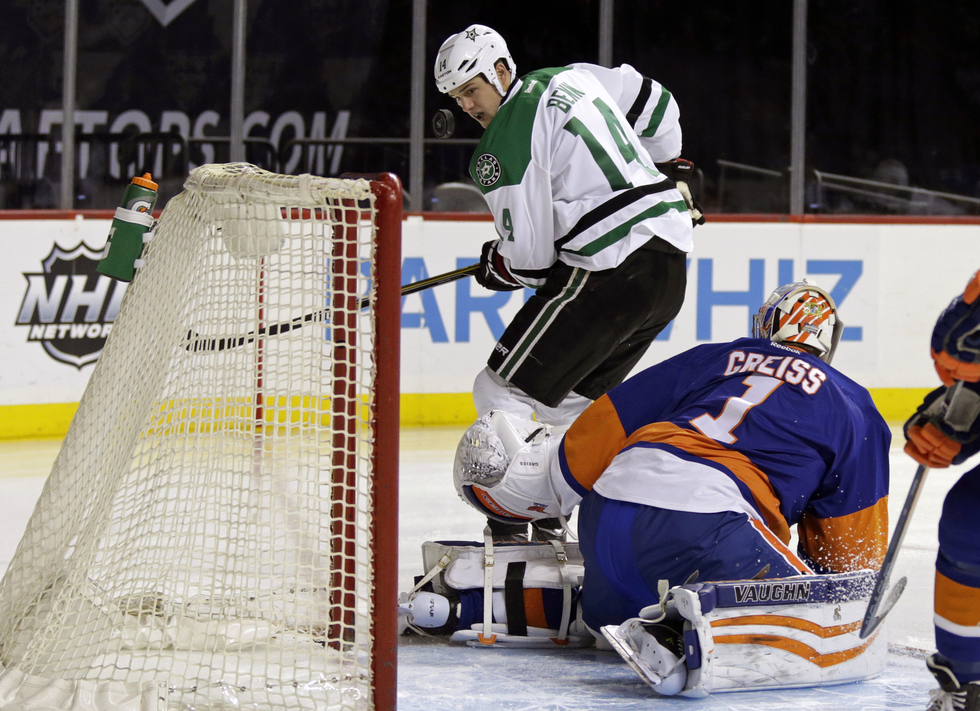 Dallas Stars left wing Jamie Benn (14) keeps his eye on the puck after New York Islanders goalie Thomas Greiss (1) made a save in the first period of an NHL hockey game Sunday, Jan. 3, 2016, in New York. (AP Photo/Adam Hunger)