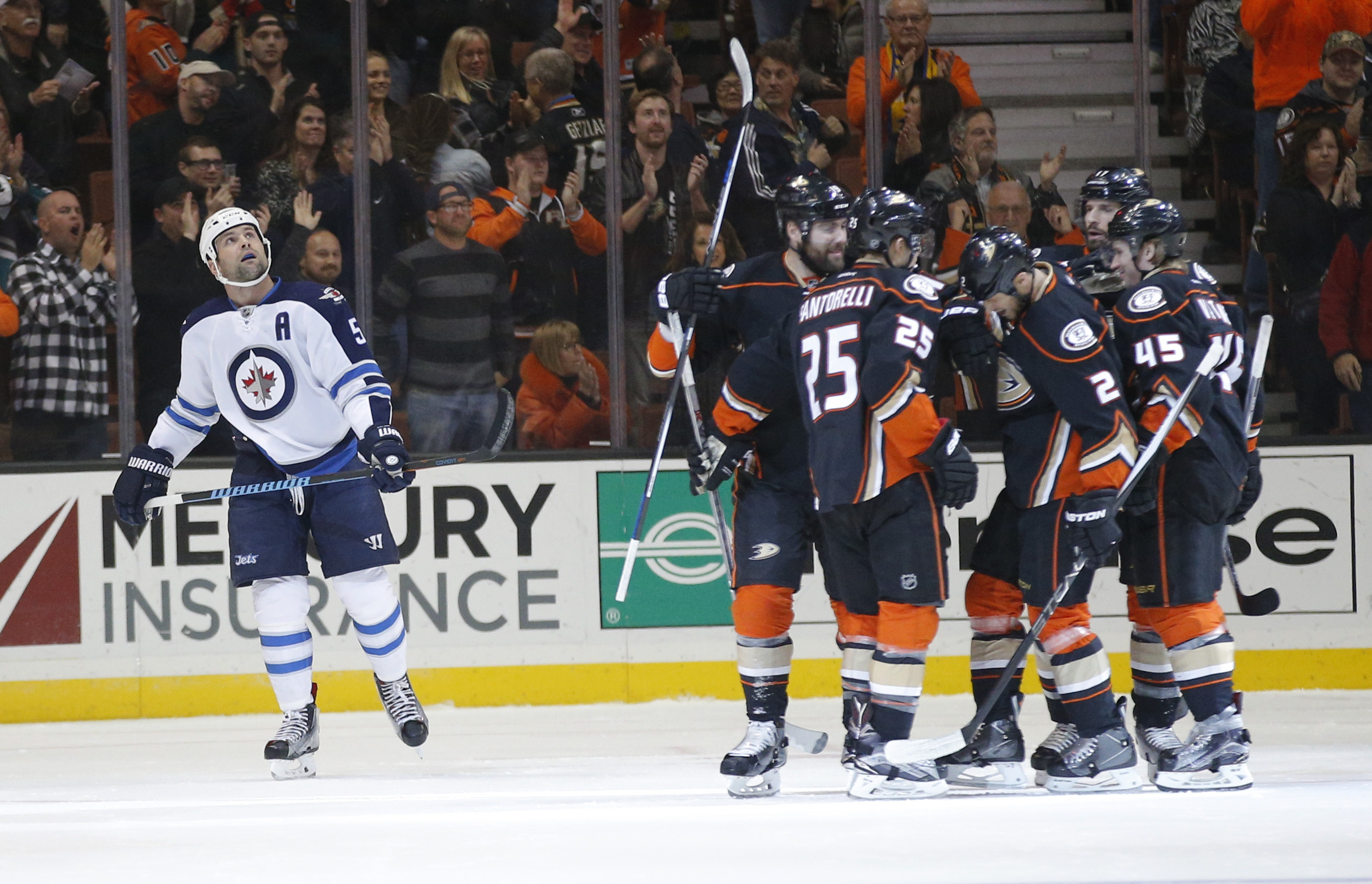 Winnipeg Jets' Mark Stuart, left, looks at the scoreboard as the Anaheim Ducks players celebrate a goal by Kevin Bieksa during the first period of an NHL hockey game, Sunday, Jan. 3, 2016, in Anaheim, Calif. (AP Photo/Jae C. Hong)