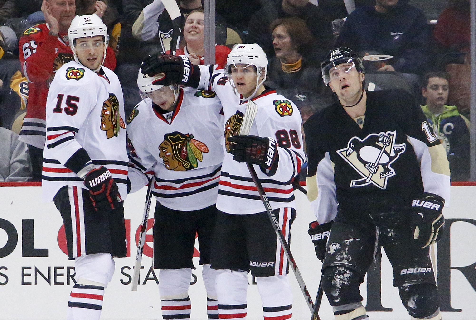 Chicago Blackhawks' Artemi Panarin, second from left, celebrates his goal with teammates Artem Anisimov (15) and Patrick Kane (88) as Pittsburgh Penguins' Ben Lovejoy (12) skates back to his bench during the second period of an NHL hockey game in Pittsbur
