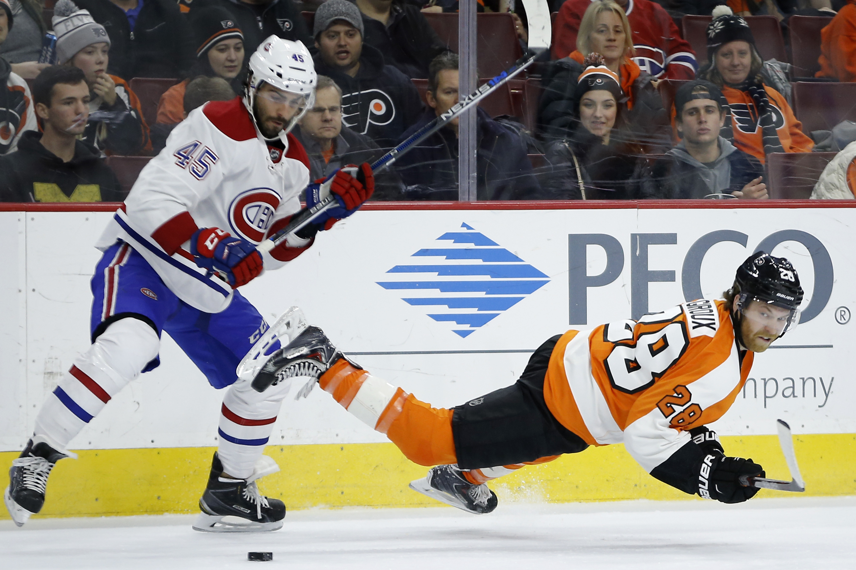 Philadelphia Flyers' Claude Giroux, right, falls after a hit from Montreal Canadiens' Mark Barberio during the second period of an NHL hockey game, Tuesday, Jan. 5, 2016, in Philadelphia. (AP Photo/Matt Slocum)
