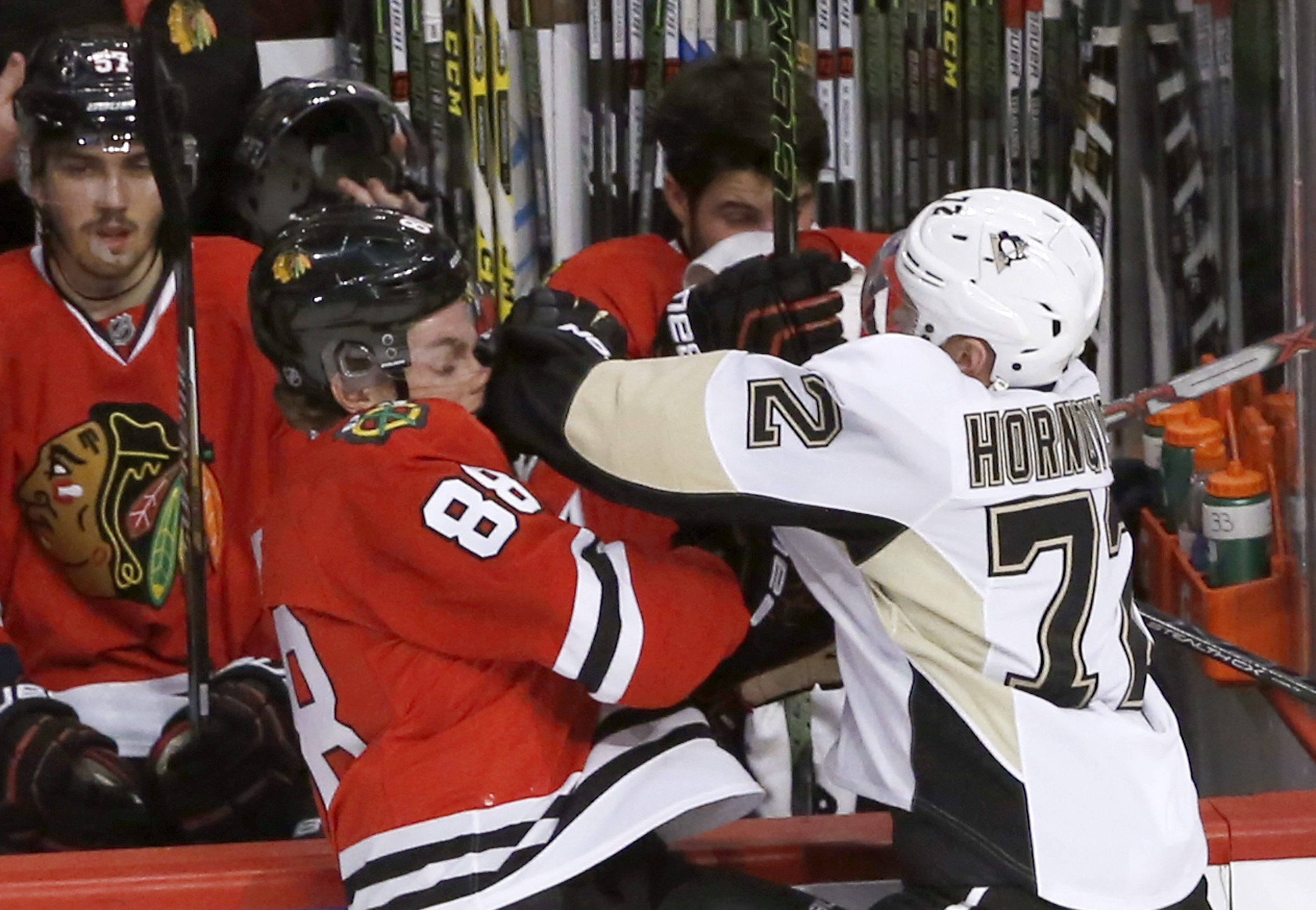 Pittsburgh Penguins right wing Patric Hornqvist (72) checks Chicago Blackhawks right wing Patrick Kane in front of the Blackhawks' bench during the first period of an NHL hockey game Wednesday, Jan. 6, 2016, in Chicago. (AP Photo/Charles Rex Arbogast)