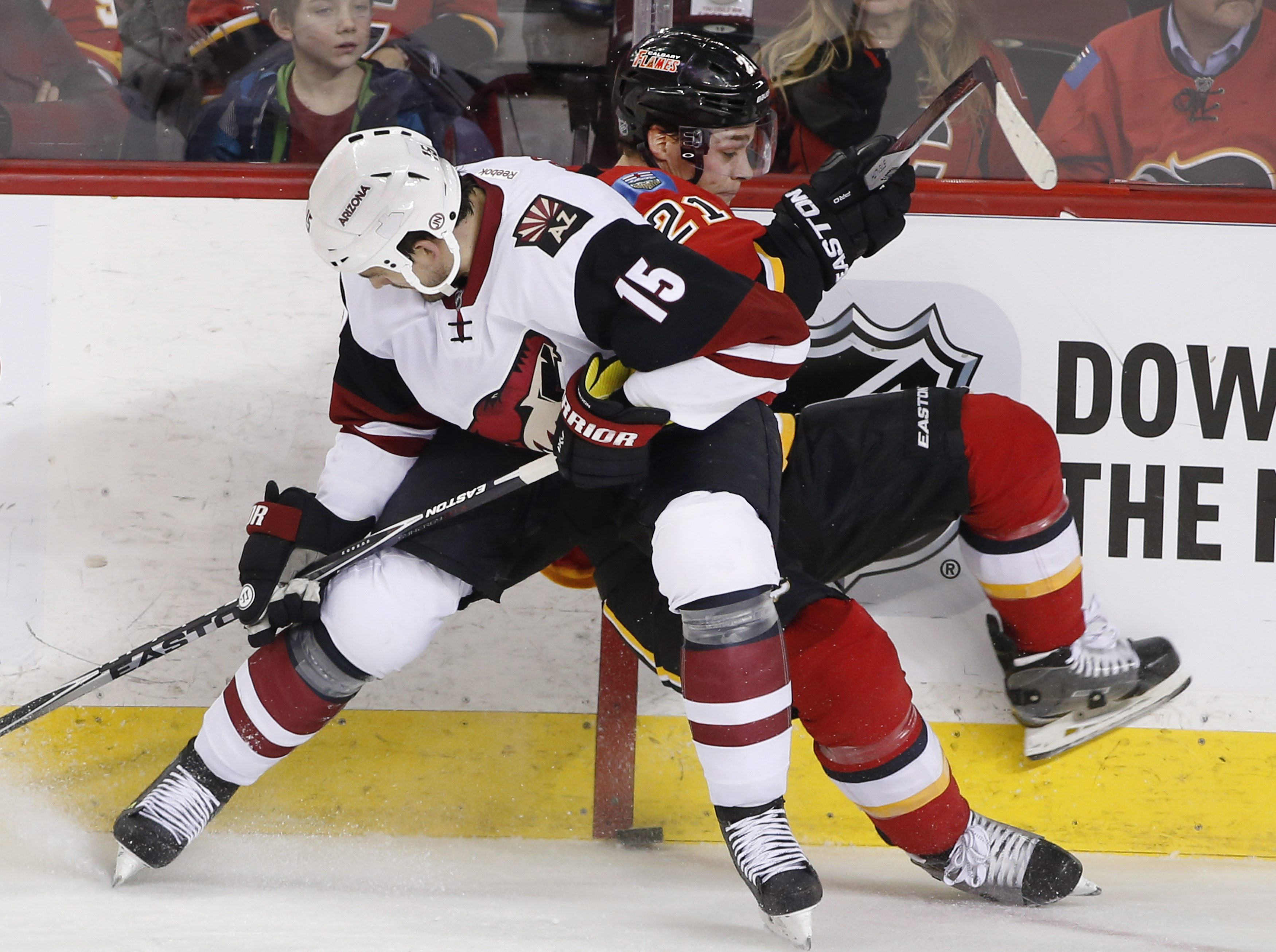 Arizona Coyotes' Boyd Gordon, left, checks Calgary Flames' Mason Raymond off the puck during the second period of an NHL hockey game Thursday, Jan. 7, 2015, in Calgary, Alberta. (Larry MacDougal/The Canadian Press via AP)