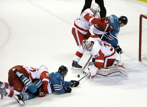 Detroit Red Wings goalie Petr Mrazek, bottom right, stops a shot next to teammate Niklas Kronwall (55) and San Jose Sharks' Joe Pavelski (8) during the first period of an NHL hockey game Thursday, Jan. 7, 2016, in San Jose, Calif. (AP Photo/Marcio Jose Sa