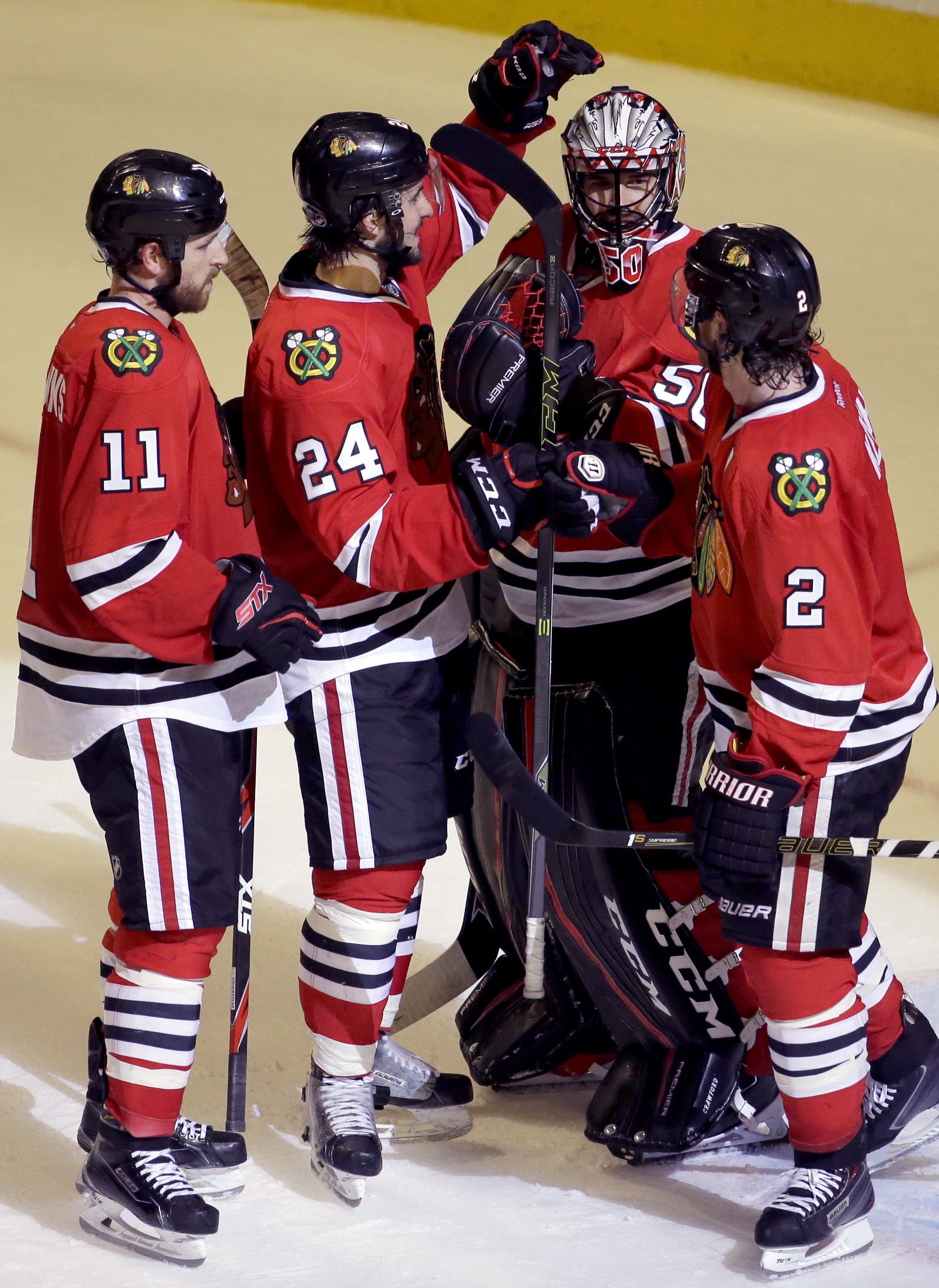 Chicago Blackhawks goalie Corey Crawford, second from right, celebrates with center Phillip Danault (24), defenseman Duncan Keith (2) and left wing Andrew Desjardins (11) after they defeated the Buffalo Sabres 3-1 in an NHL hockey game Friday, Jan. 8, 201