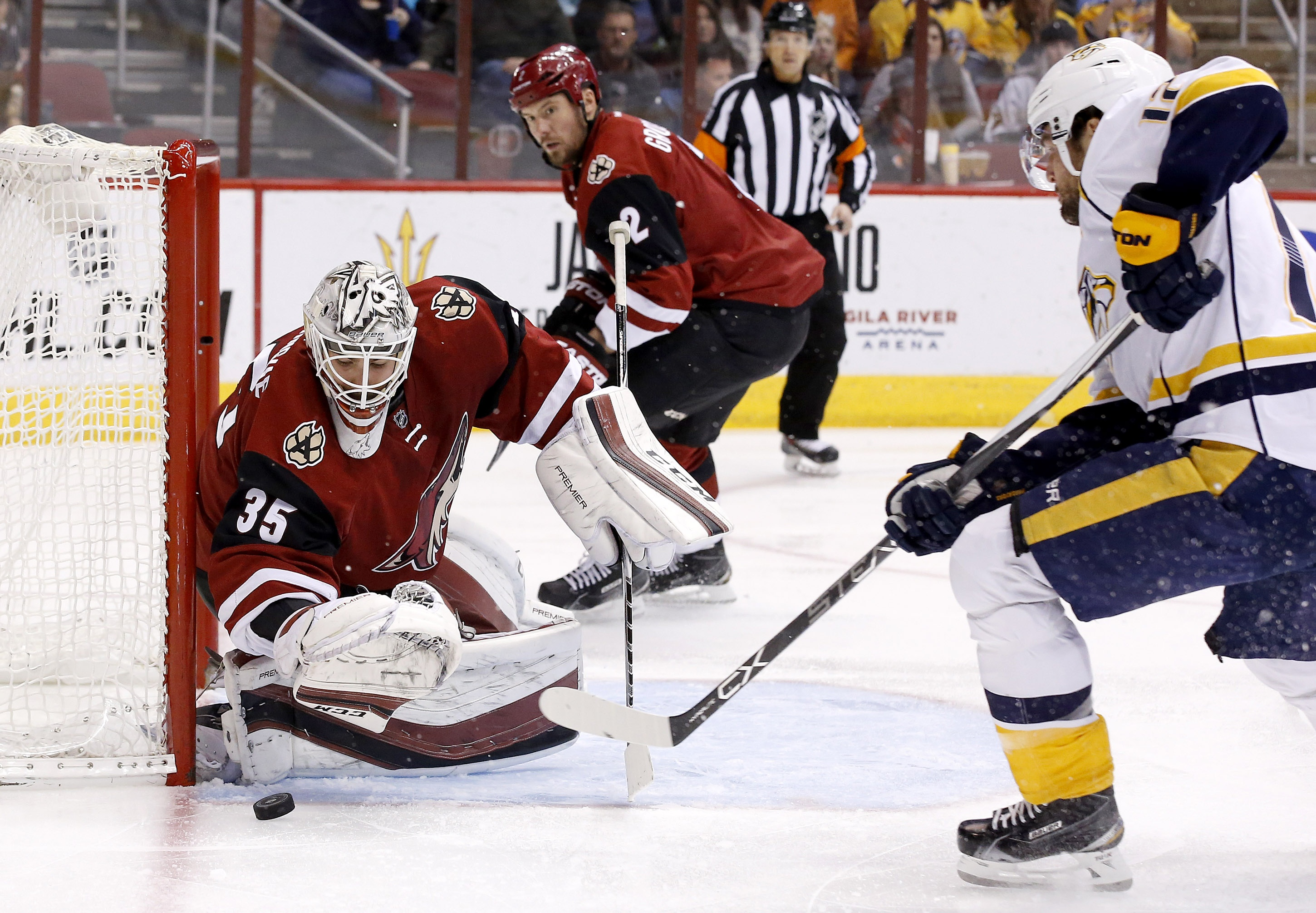 Arizona Coyotes' Louis Domingue (35) makes a save on a shot by Nashville Predators' Mike Fisher, right, as Coyotes' Nicklas Grossmann (2), of Sweden, watches during the first period of an NHL hockey game Saturday, Jan. 9, 2016, in Glendale, Ariz. (AP Phot