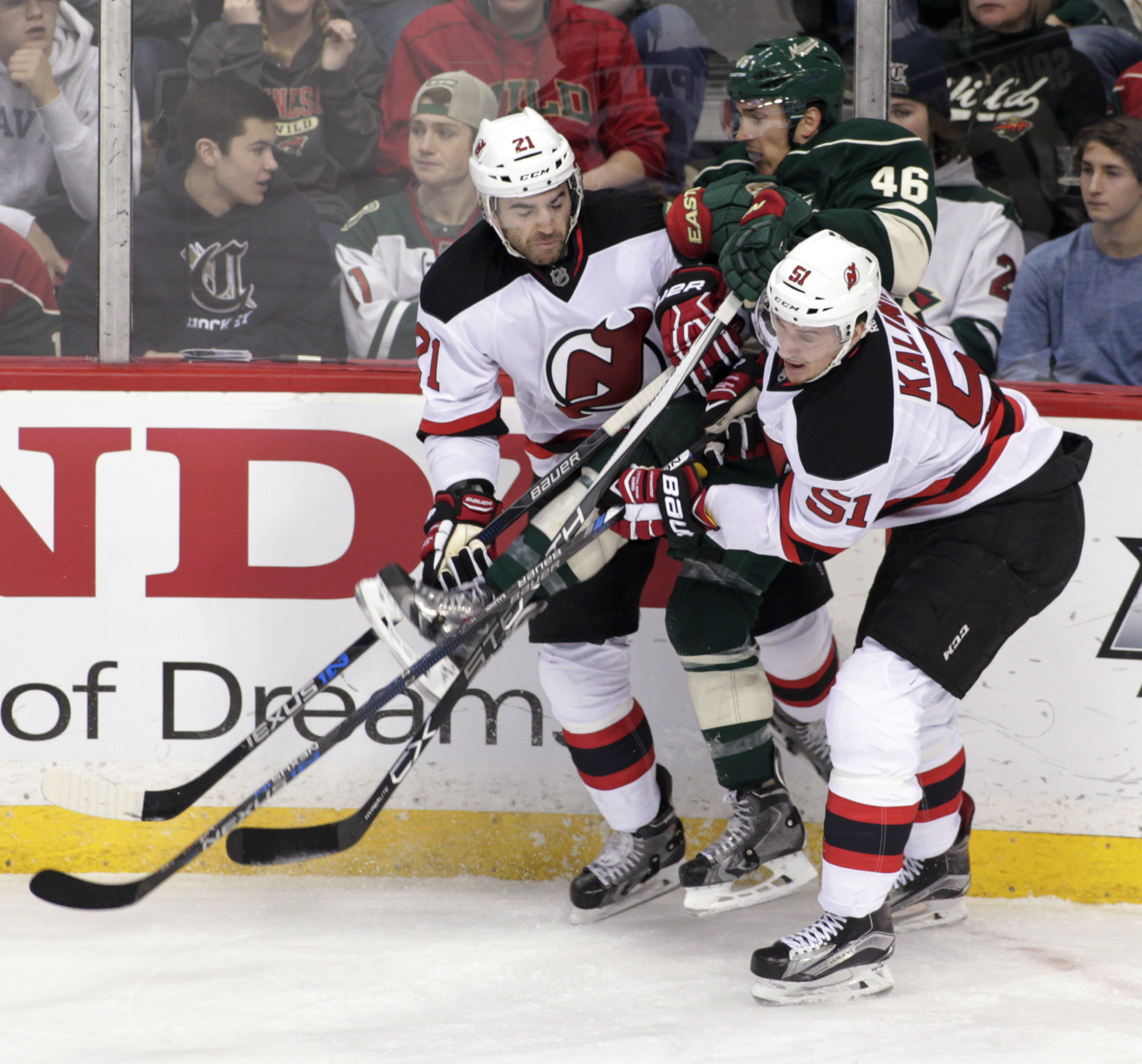 Minnesota Wild defenseman Jared Spurgeon (46) is sandwiched by New Jersey Devils' Kyle Palmieri (21) and Sergey Kalinin (51), of Russia, during the first period of an NHL hockey game Sunday, Jan. 10, 2016, in St. Paul, Minn. (AP Photo/Paul Battaglia)