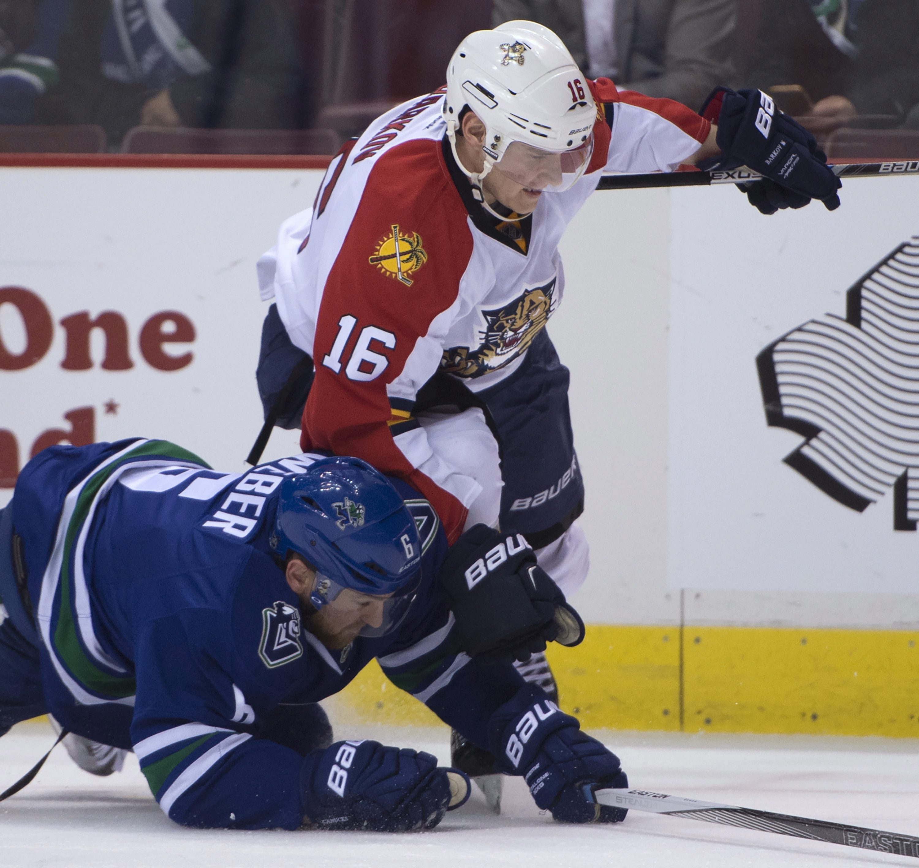 Vancouver Canucks defenseman Yannick Weber (6) fights for control of the puck with Florida Panthers center Aleksander Barkov (16) during first period NHL hockey action in Vancouver, British Columbia, Canada, Monday, Jan. 11, 2016. (Jonathan Hayward/The Ca