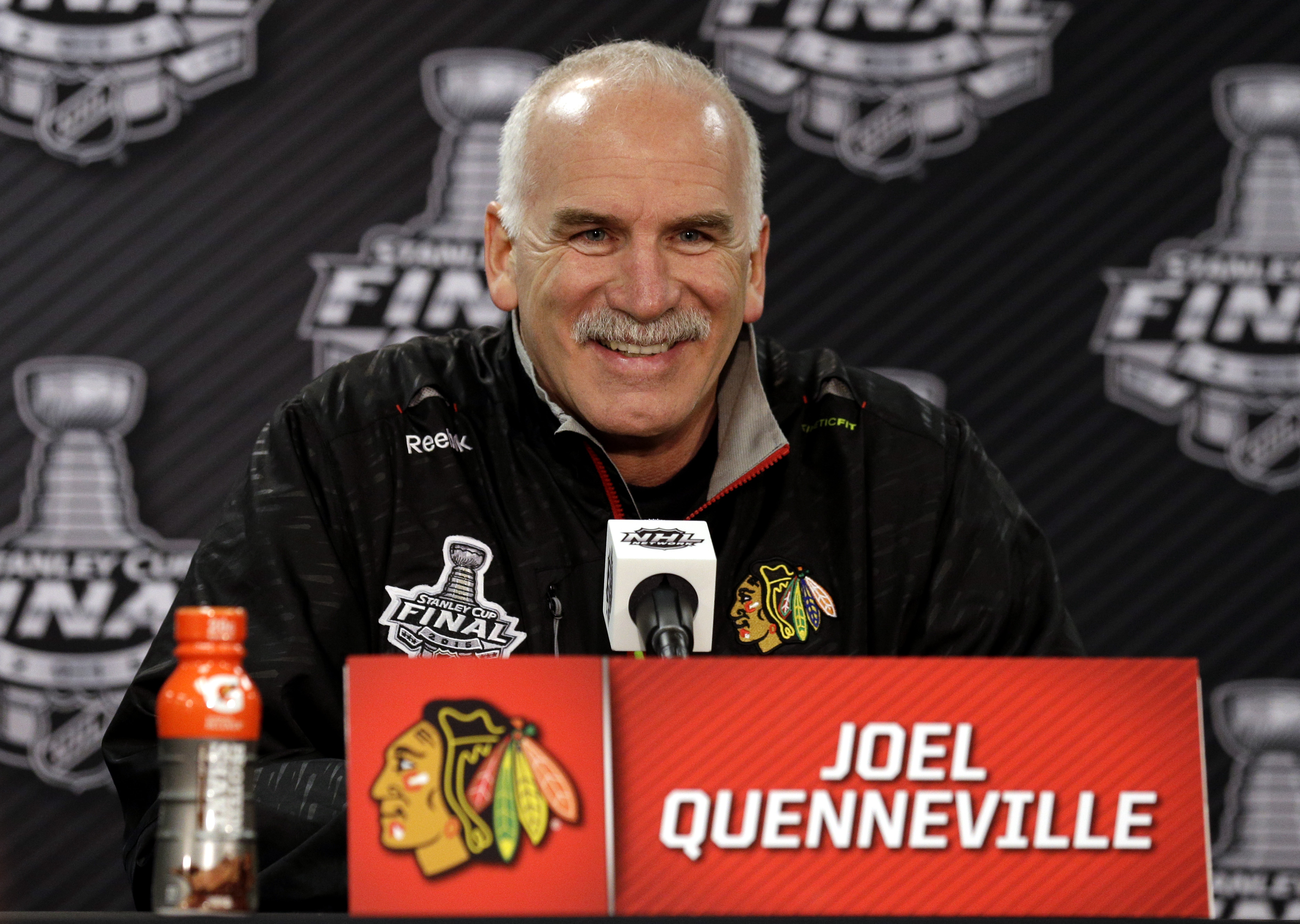 FILE - In this June 7, 2015, file photo, Chicago Blackhawks head coach Joel Quenneville smiles as he talks during a news conference in Chicago. The Chicago Blackhawks have given a three-year contract extension to Joel Quenneville, locking up the highly su