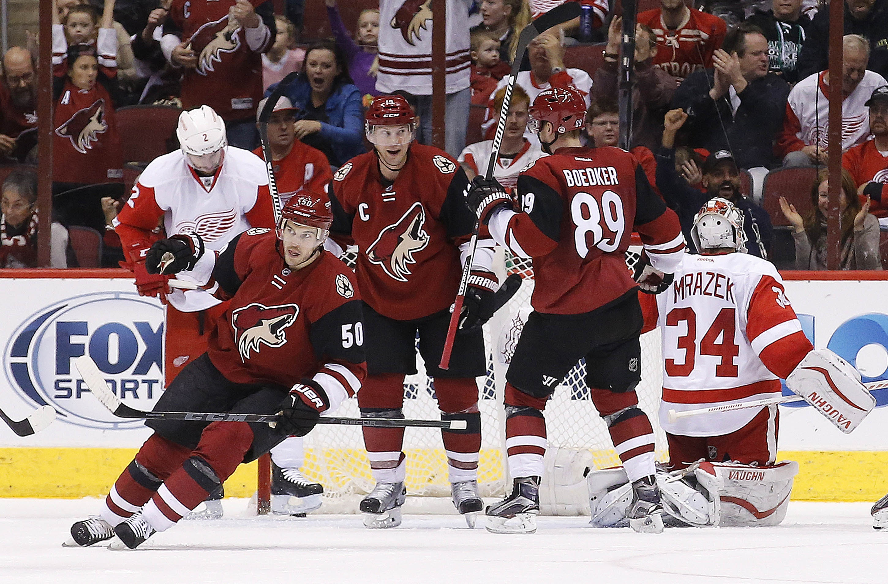 Arizona Coyotes' Mikkel Boedker (89), of Denmark, and Antoine Vermette (50) celebrate a goal by Shane Doan, middle, against Detroit Red Wings' Petr Mrazek (34), of the Czech Republic, as Red Wings' Brendan Smith (2) looks away from the celebration during