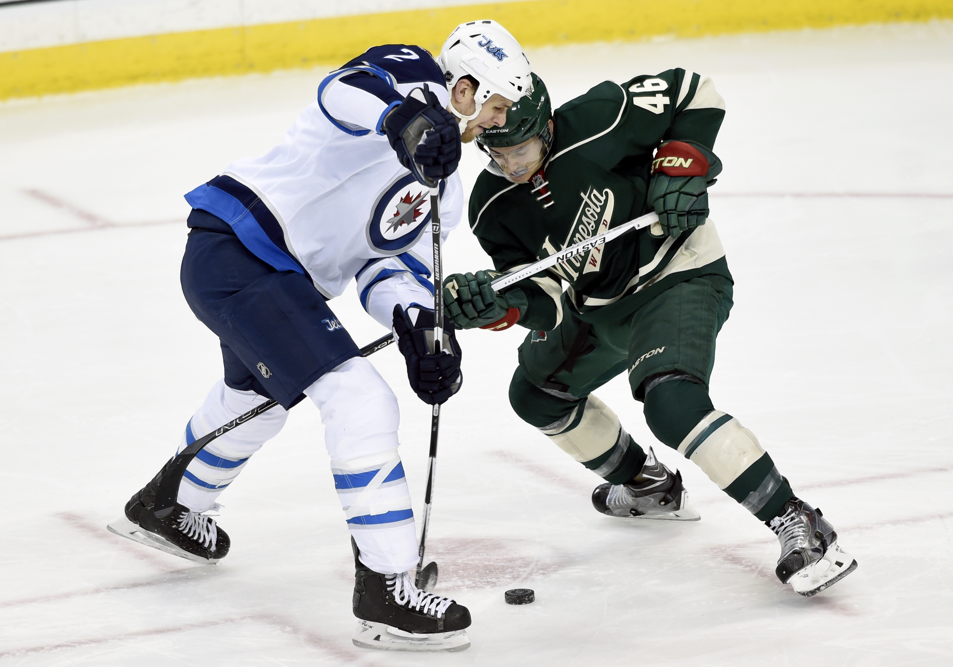 Winnipeg Jets defenseman Adam Pardy (2) keeps the puck away from Minnesota Wild defenseman Jared Spurgeon (46) during the first period of an NHL hockey game Friday, Jan. 15, 2016, in St. Paul, Minn. (AP Photo/Hannah Foslien)