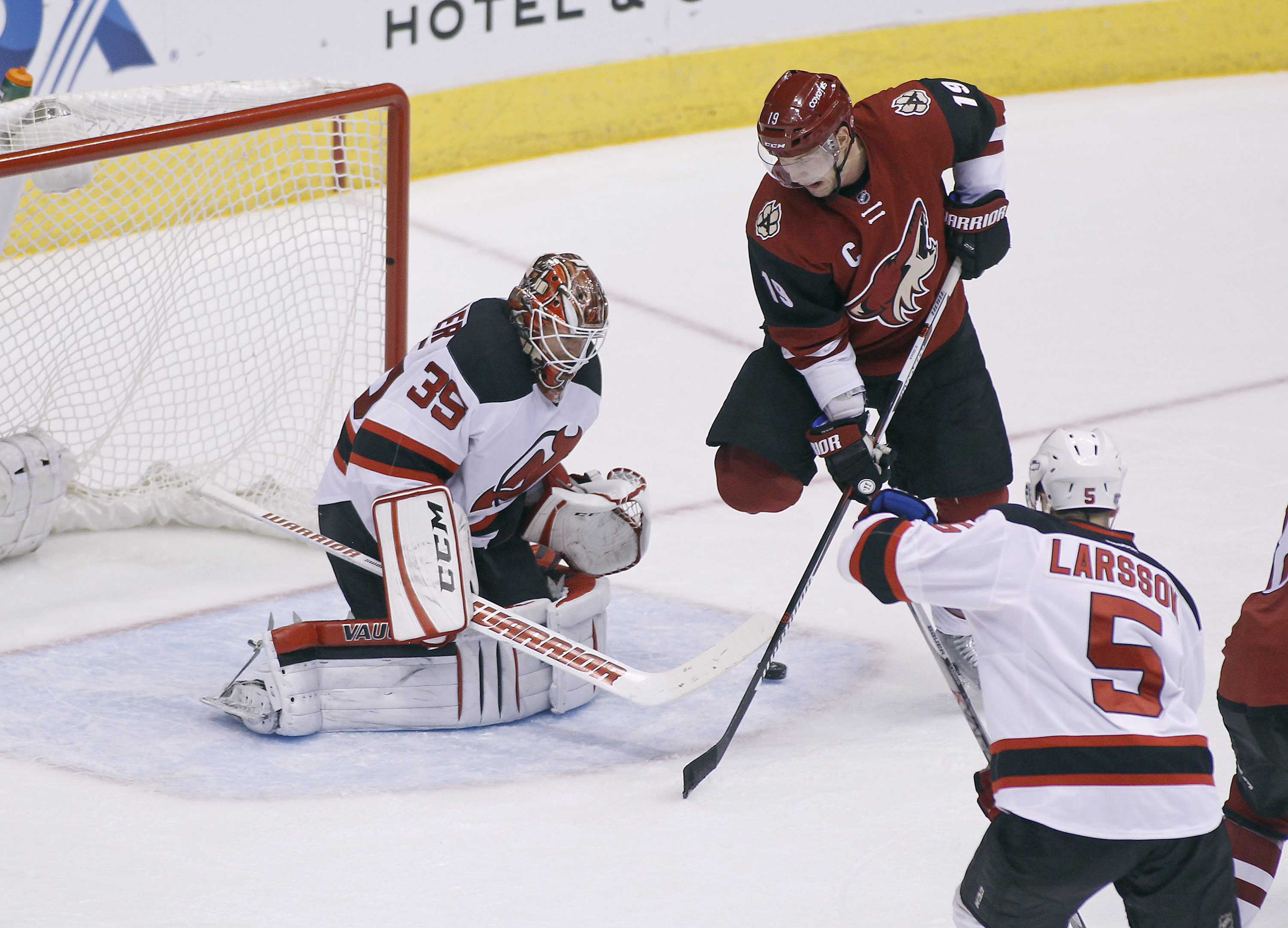 Arizona Coyotes' Shane Doan (19) tries to re-direct the puck past New Jersey Devils goalie Cory Schneider (35) as the Devil's Adam Larsson (5), of Sweden, defends during the second period of an NHL hockey game, Saturday, Jan. 16, 2016, in Glendale, Ariz.