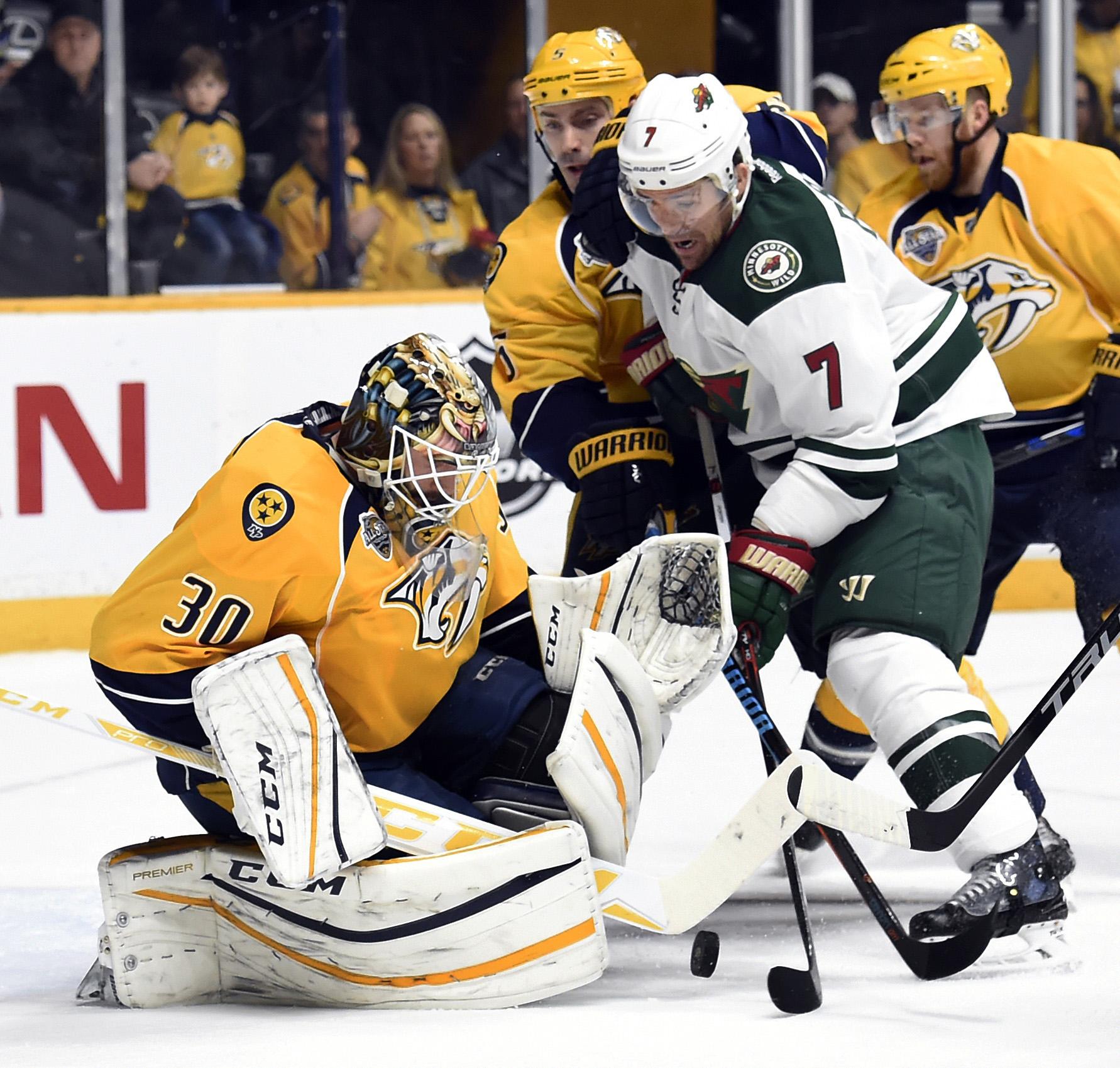 Nashville Predators goalie Carter Hutton (30) stops a shot by Minnesota Wild left wing Chris Porter (7) during the first period of an NHL hockey game Saturday, Jan. 16, 2016, in Nashville, Tenn. (AP Photo/Mark Zaleski)