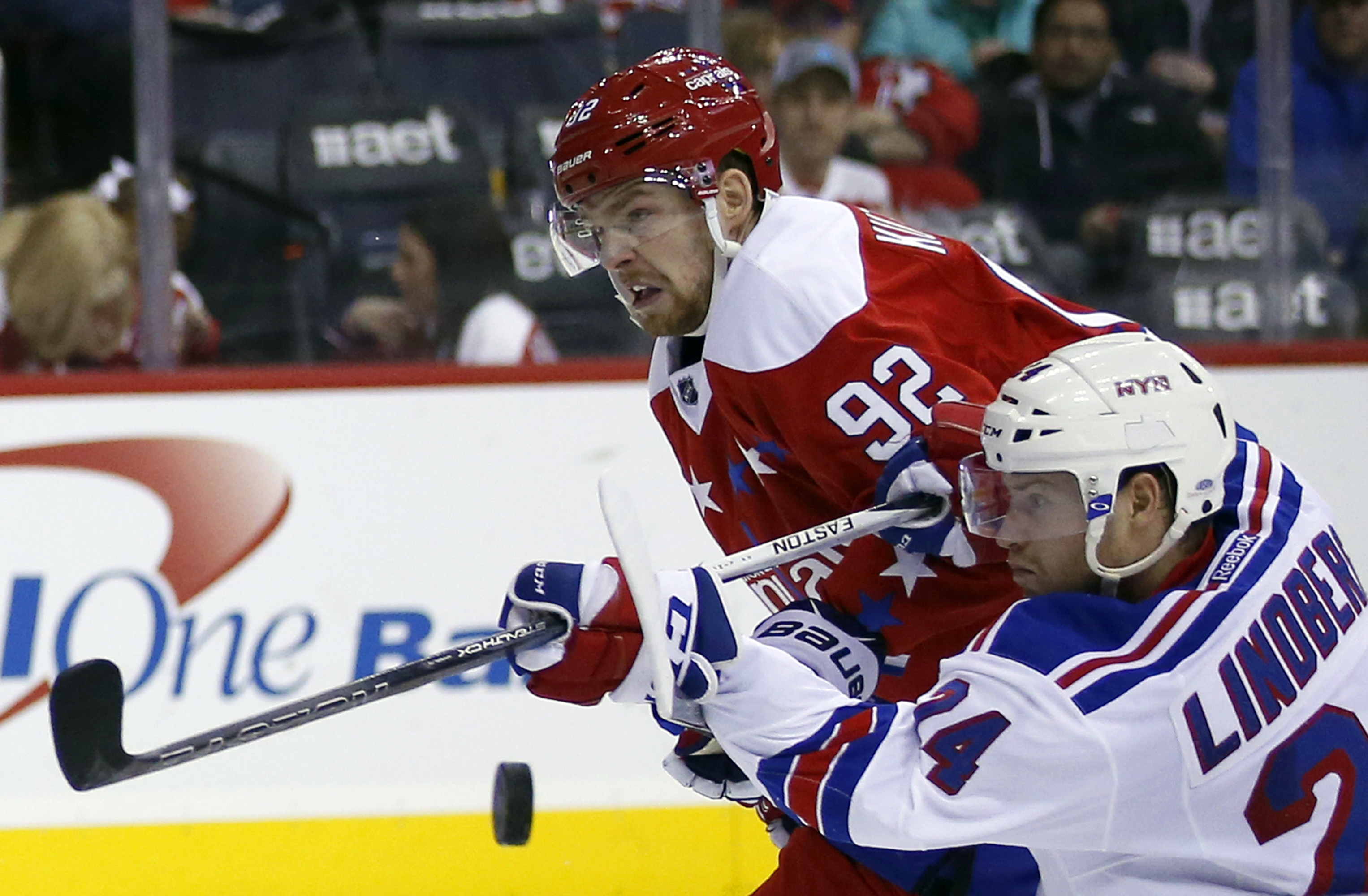 New York Rangers center Oscar Lindberg (24), from Sweden, tries to hit the puck as Washington Capitals center Evgeny Kuznetsov (92), from Russia, defends in the second period of an NHL hockey game, Sunday, Jan. 17, 2016, in Washington. (AP Photo/Alex Bran