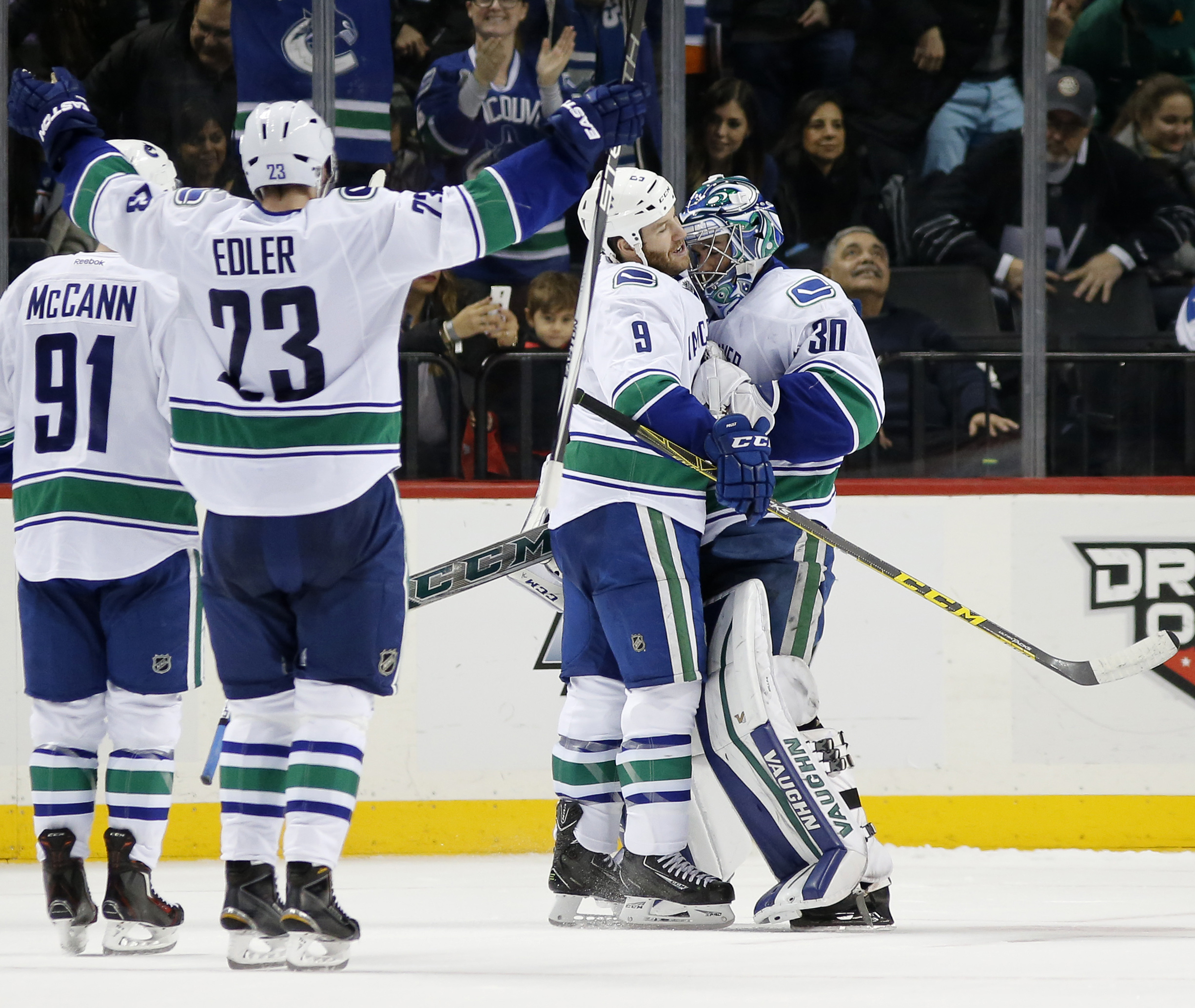 Vancouver Canucks right wing Brandon Prust (9) embraces Canucks goalie Ryan Miller (30) as Canucks defenseman Alexander Edler (23), of Sweden, celebrates after they defeated the New York Islanders 2-1 in a shootout in overtime of an NHL hockey game in New
