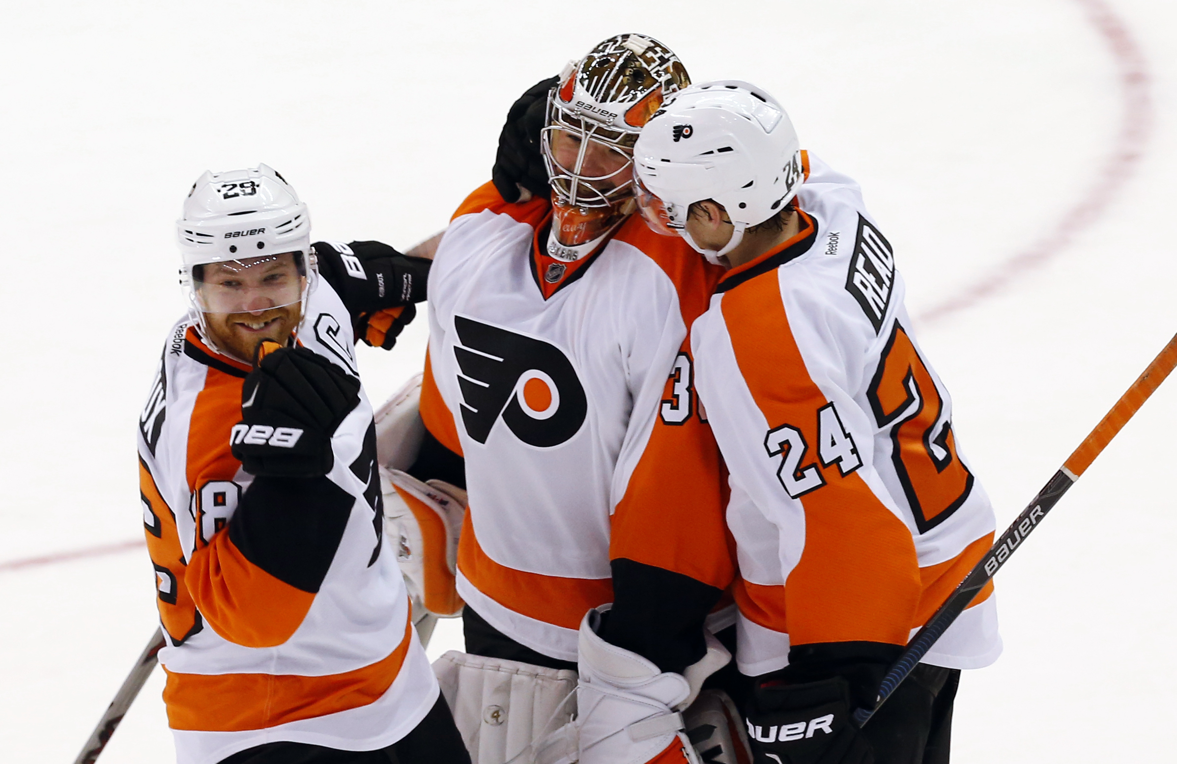 Philadelphia Flyers center Claude Giroux, from left, goalie Michal Neuvirth and Matt Read (24) celebrate after a shootout against the Detroit Red Wings in an NHL hockey game, Sunday, Jan. 17, 2016 in Detroit. Philadelphia won 2-1. (AP Photo/Paul Sancya)