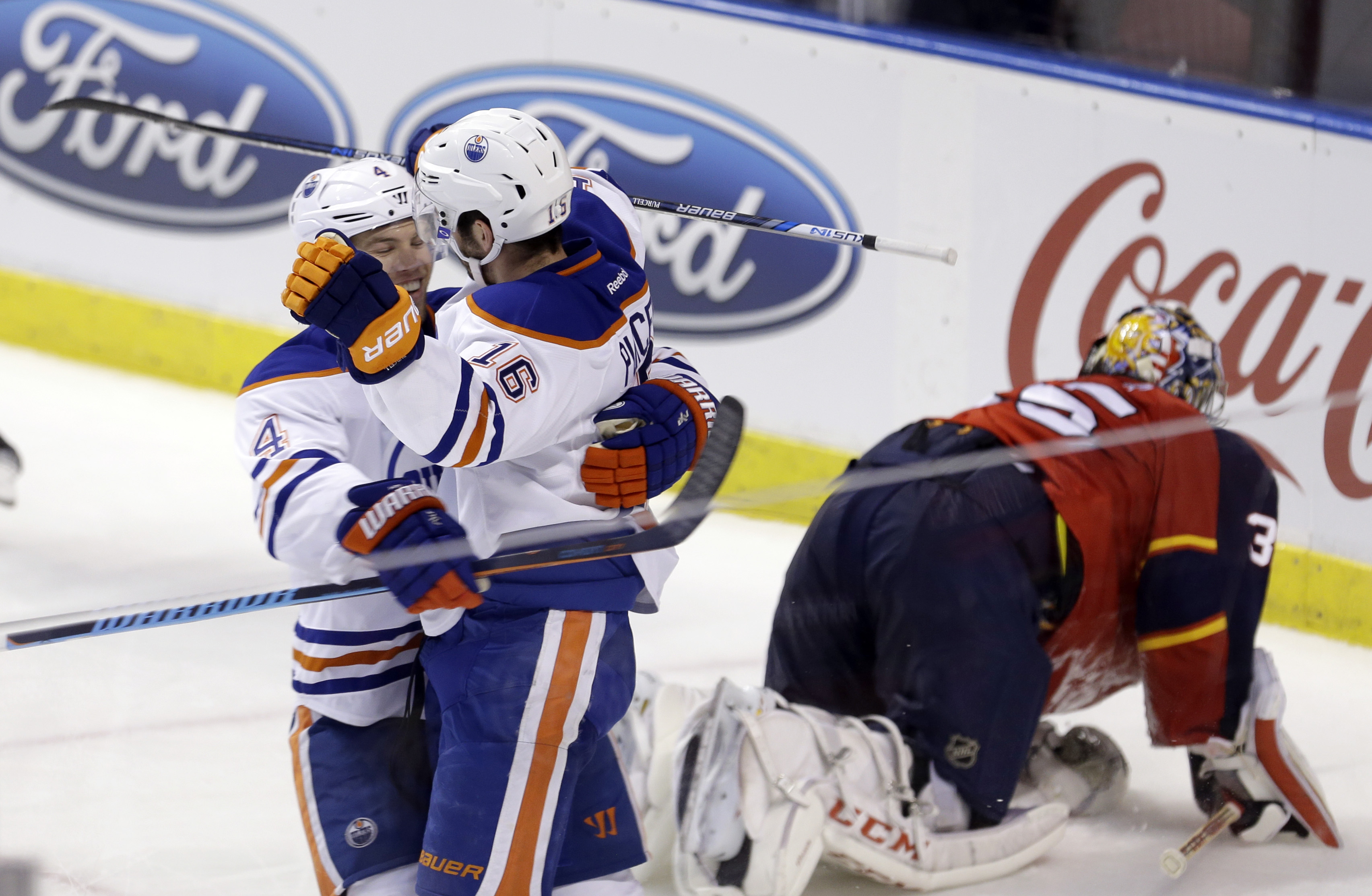 Edmonton Oilers left wing Taylor Hall (4) congratulates teammate Teddy Purcell (16) after Purcell scored against the Florida Panthers during the third period of an NHL hockey game, Monday, Jan. 18, 2016, in Sunrise, Fla. The Oilers won 4-2. (AP Photo/Alan