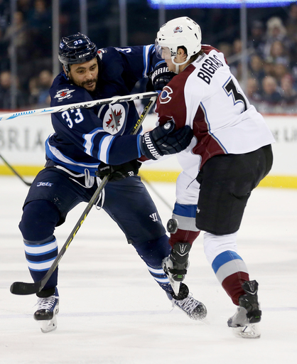 Winnipeg Jets' Dustin Byfuglien (33) shoves past Colorado Avalanche's Chris Bigras (3) during second period NHL hockey action in Winnipeg, Monday, Jan. 18, 2016. (Trevor Hagan/The Canadian Press via AP)