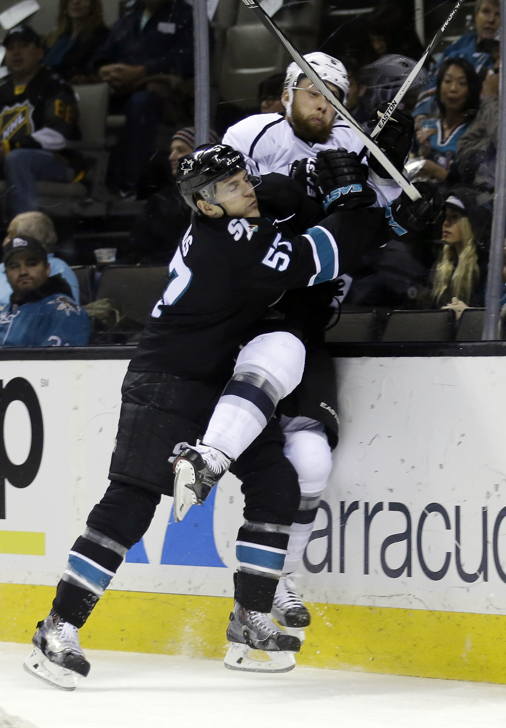 San Jose Sharks' Tommy Wingels, left, collides with Los Angeles Kings' Jake Muzzin during the first period of an NHL hockey game, Sunday, Jan. 24, 2016, in San Jose, Calif. (AP Photo/Marcio Jose Sanchez)